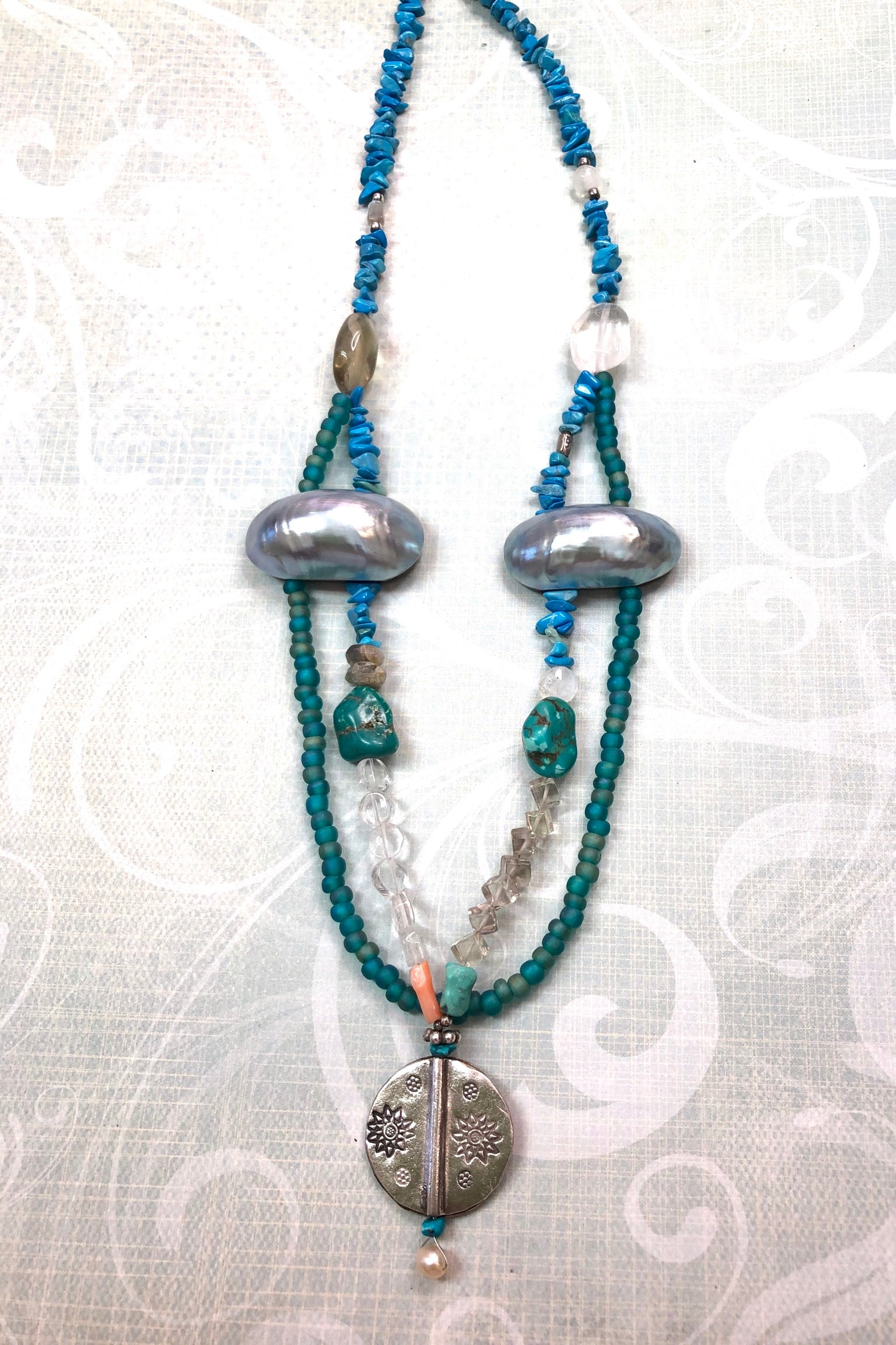 Necklace Echo Sea and Stars has a silver bead from Thai Hill Tribes in centre and Other stones include Howlite, coral,turquoise, rock crystal, mother of pearl shell, glass beads and smokey quartz.