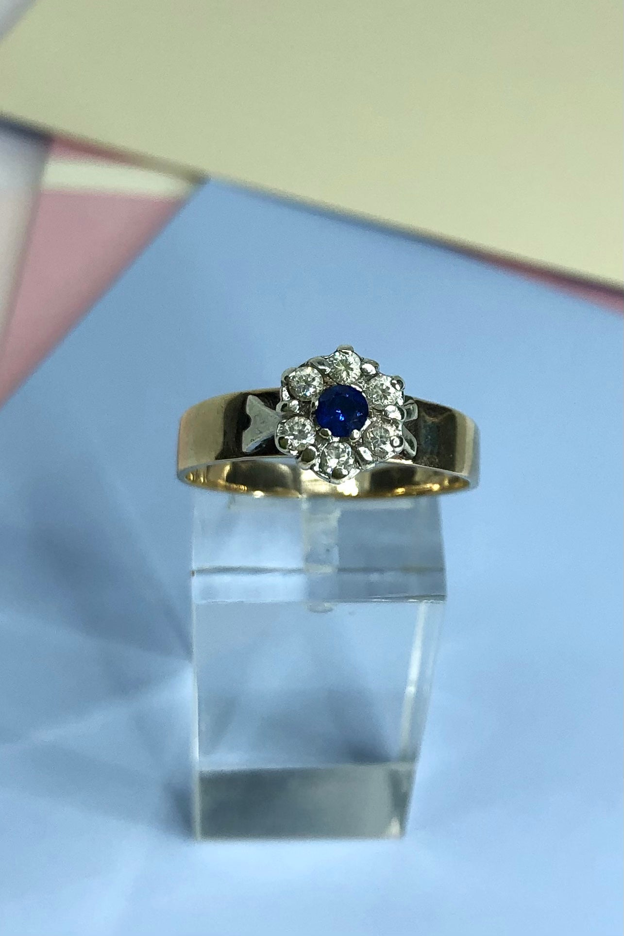 This Vintage ring features a very high setting, a small clear blue sapphire is halo set with six old cut white topaz.