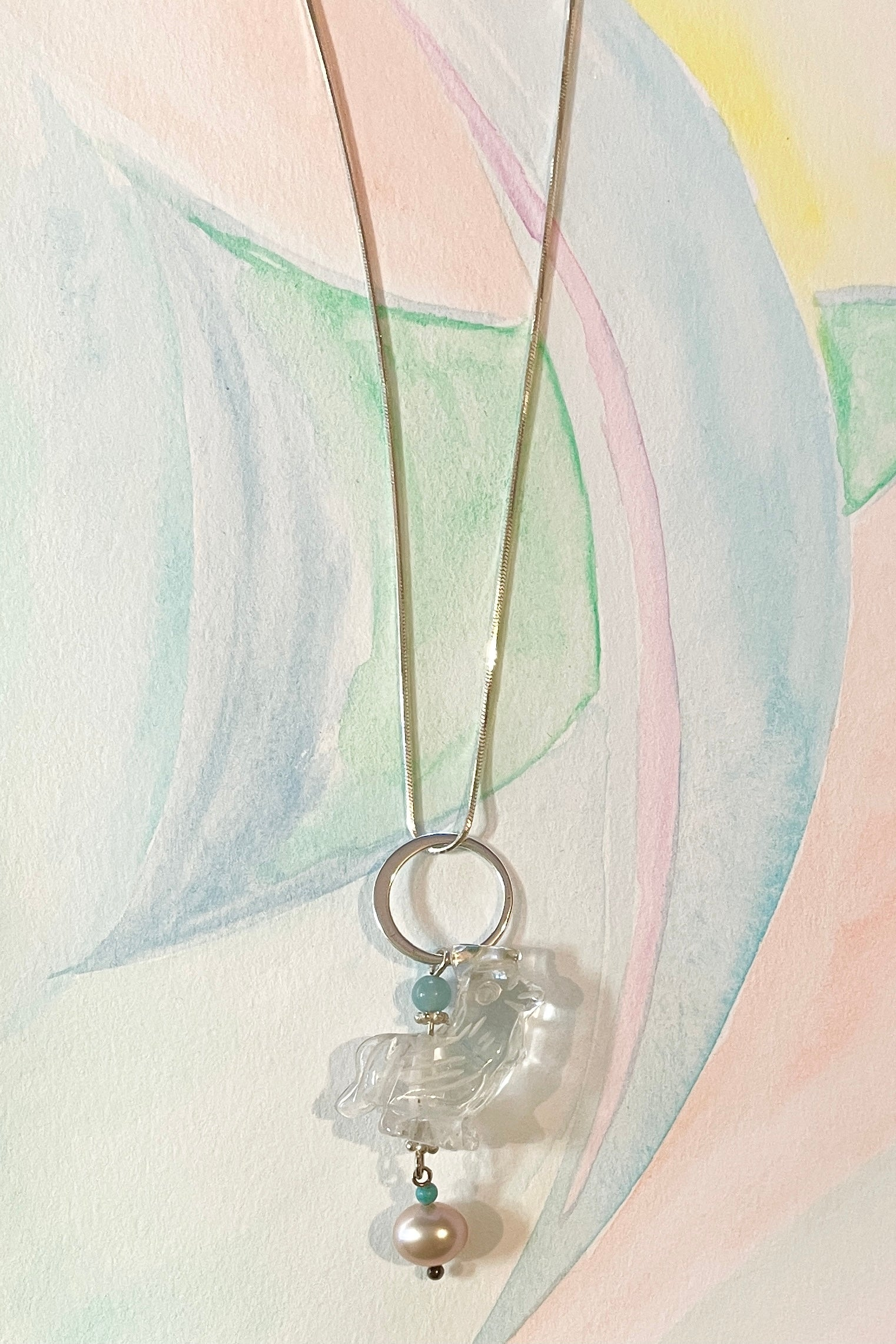 A little hand carved rock crystal rooster on a silver chain. With Amazonite and turquoise beads, a lovely pink pearl hangs at the base, this makes pendant perfection.