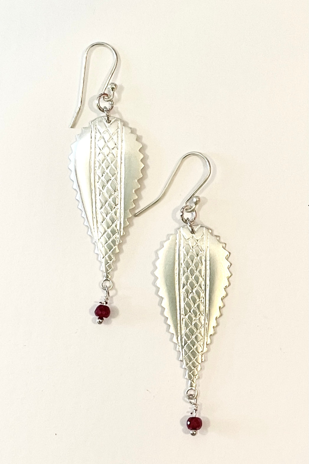 earrings In 925 silver with a small ruby bead suspended from the base.