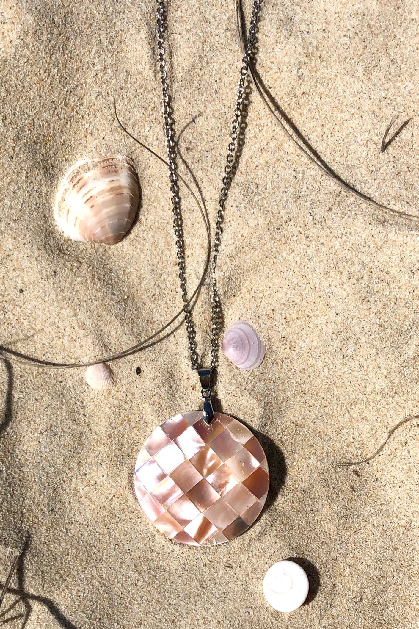 A beautiful pendant with a mother of pearl mosaic surface, it is a soft pinky gold gleaming mother of pearl shell that has been applied to a base of shell,