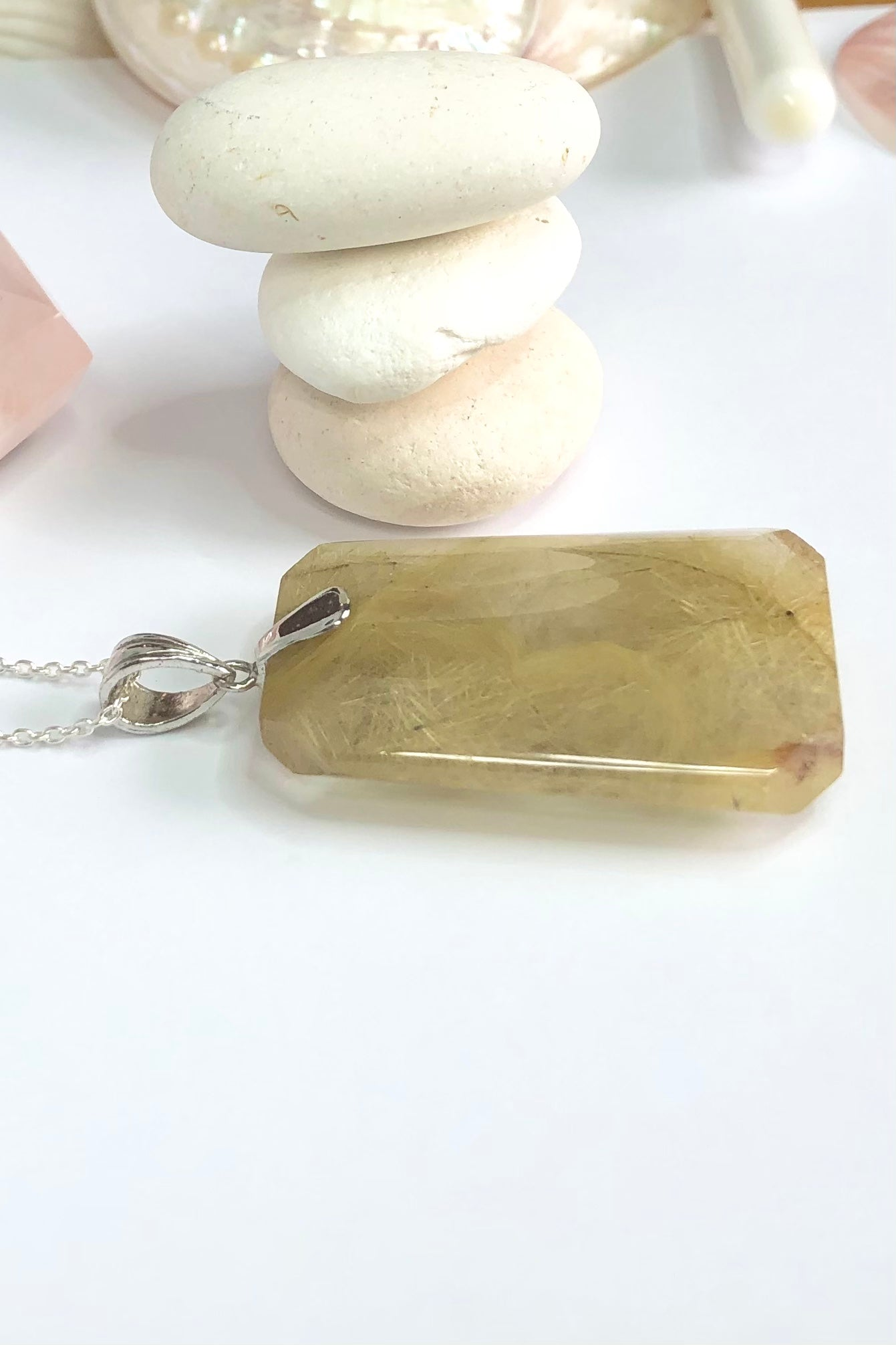 The Purity of a lovey natural crystal pendant polished to a high shine, this stone is cut into a strong angular shape with the Gold Rutile needles dense throughout.