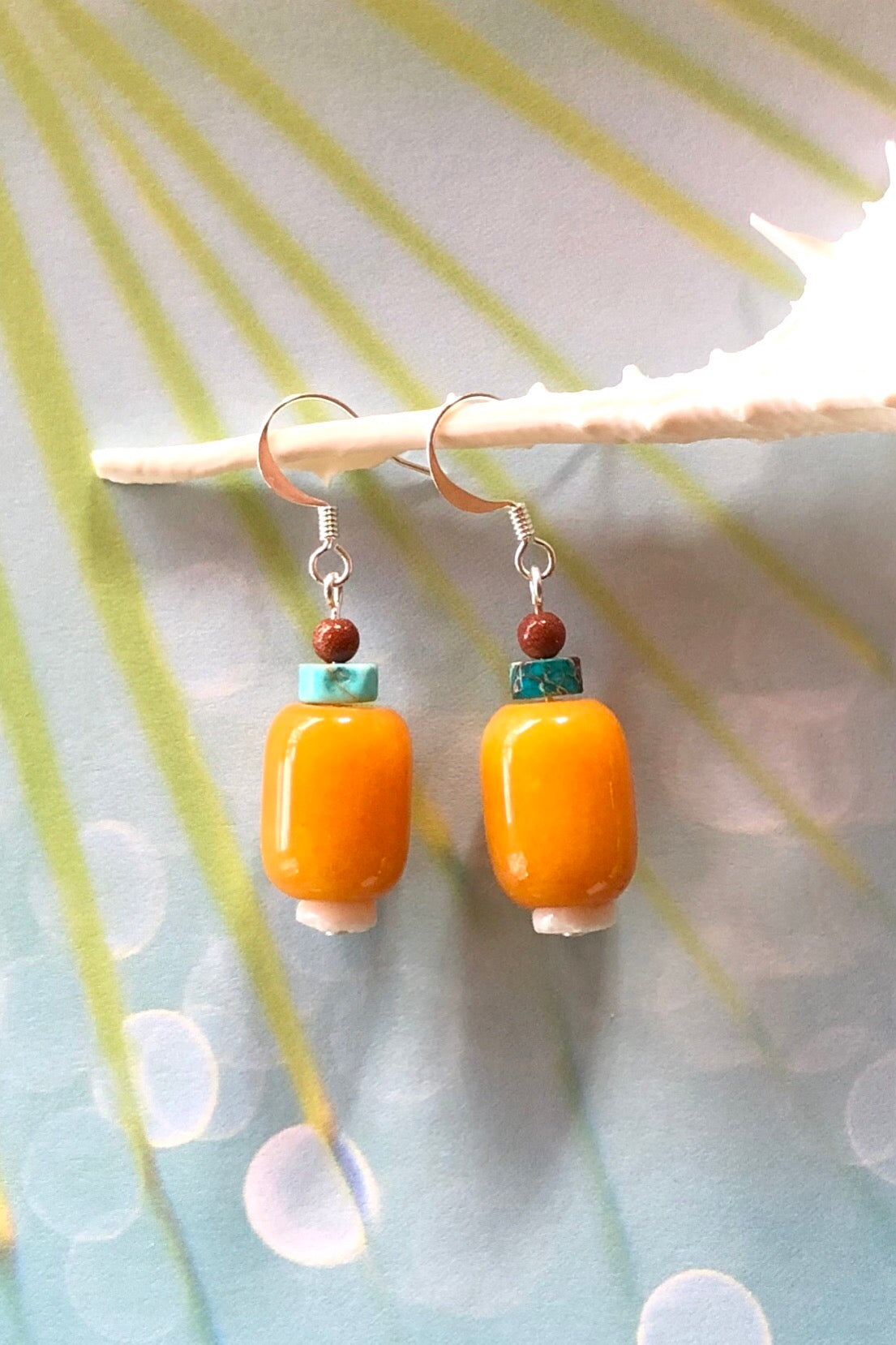 Samara May Lantern earrings are handmade drop style earrings featuring turquoise howlite, shell bead, sunstone, quartz and those stones are village cut.