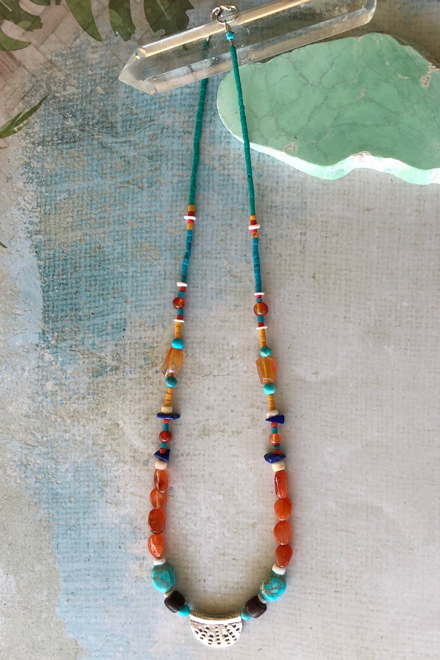 Necklace Cay Silver Curve Turquoise has pretty little beads featuring Carnelian, turquoise Howlite, shell, wood, lapis lazuli and Turkish glass beads and hill tribe silver centre piece with stamping detail.