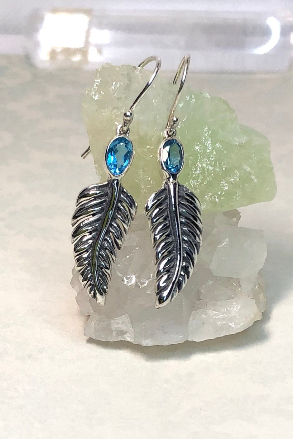 An earring that can be worn anytime at all this perfect little silver leaf is topped with a faceted bright blue topaz gemstone. Set in 925 silver.