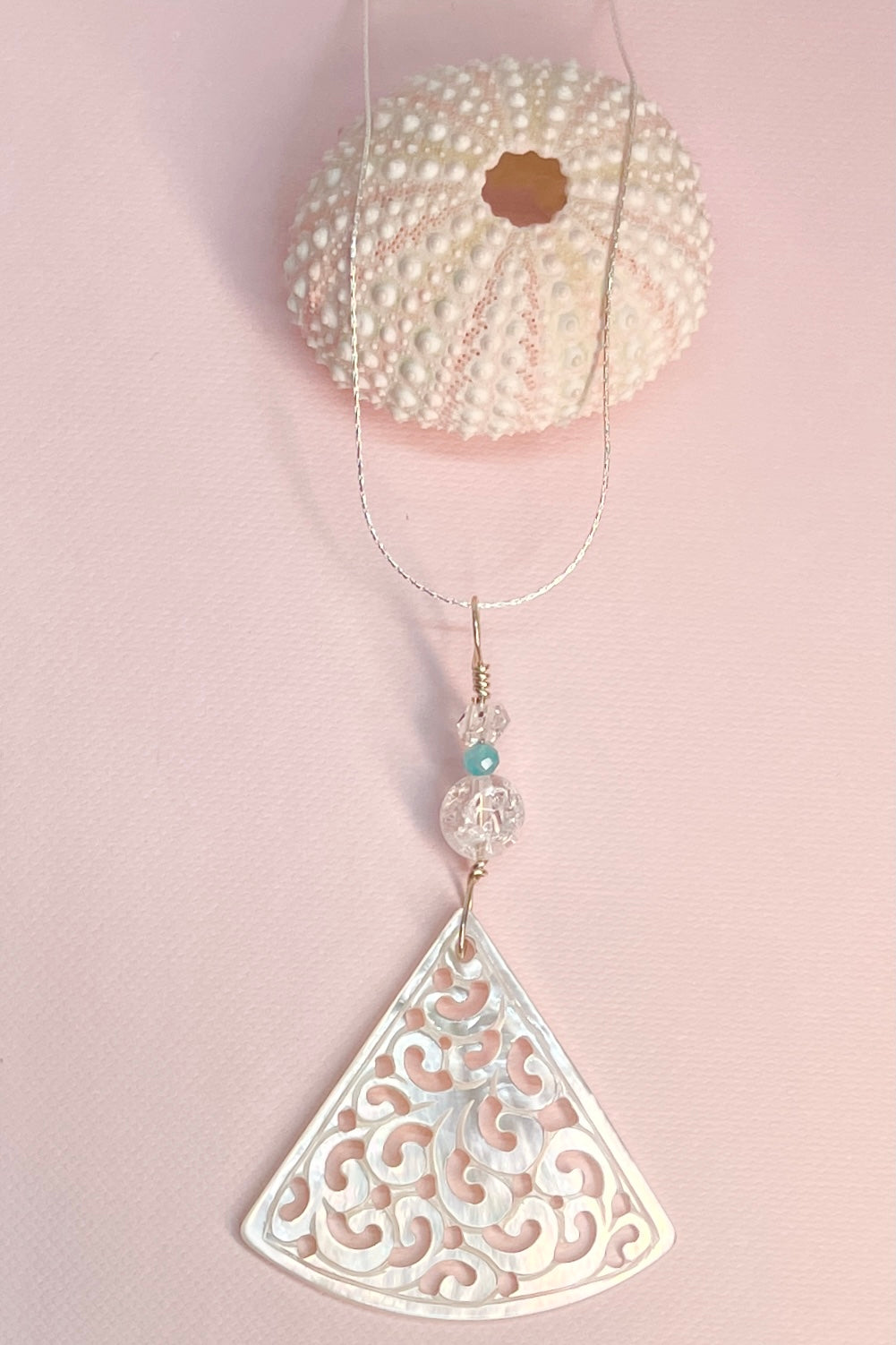 The Pendant Cay Caribbean Scrolls is hand cut from a mother of pearl shell, it has a chunk of crackle quartz to set off the pearly lustre in the shell,