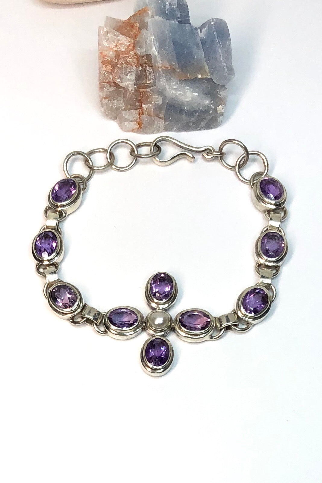 each faceted Amethyst gemstone in the Bracelet Amethyst Pearl has been cut to enhance the gorgeous mauve colour. Each of the ten stones  has been individually set and rim set into 925 silver.  The centre piece is a flower with a pearl centre.