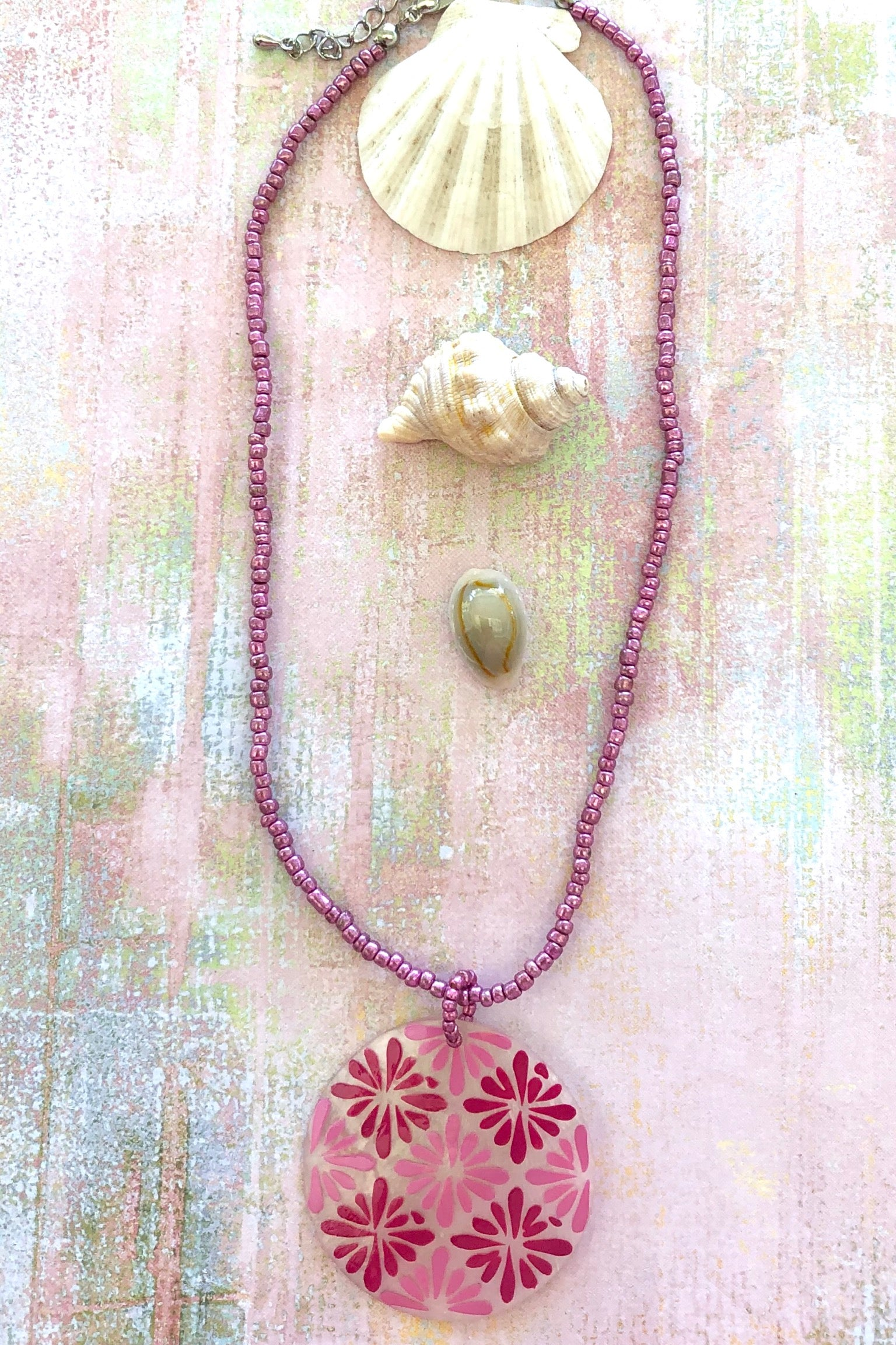This sweetheart Necklace Beach is made from small irregular beads in pale pinky mauve and the centre is a Capiz shell circle painted with 60's style daisies.