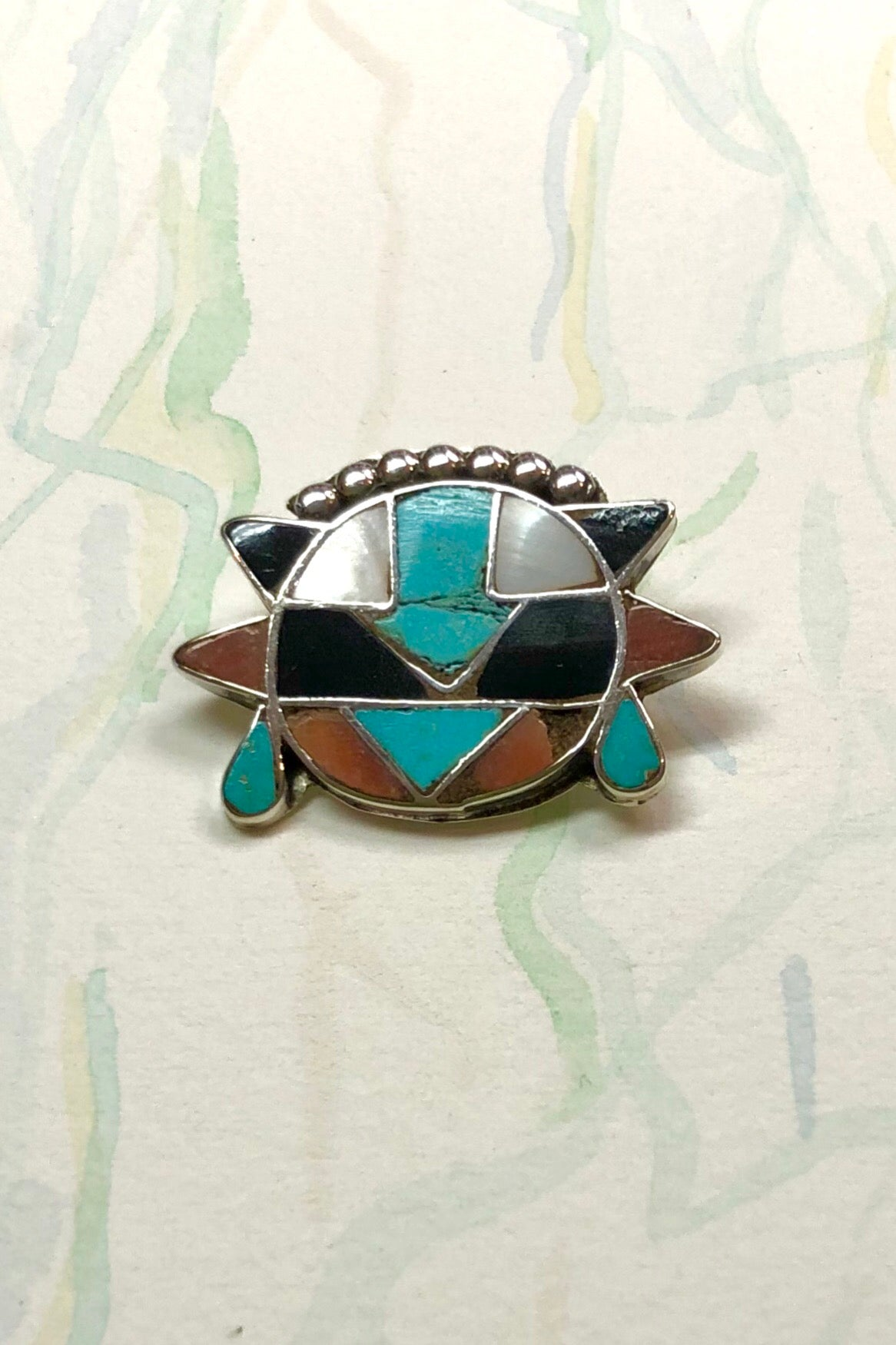 Echo Brooch Zuni Silver and Turquoise Inlay is a mysterious design brooch featuring turquoise stone, Coral and Shell.