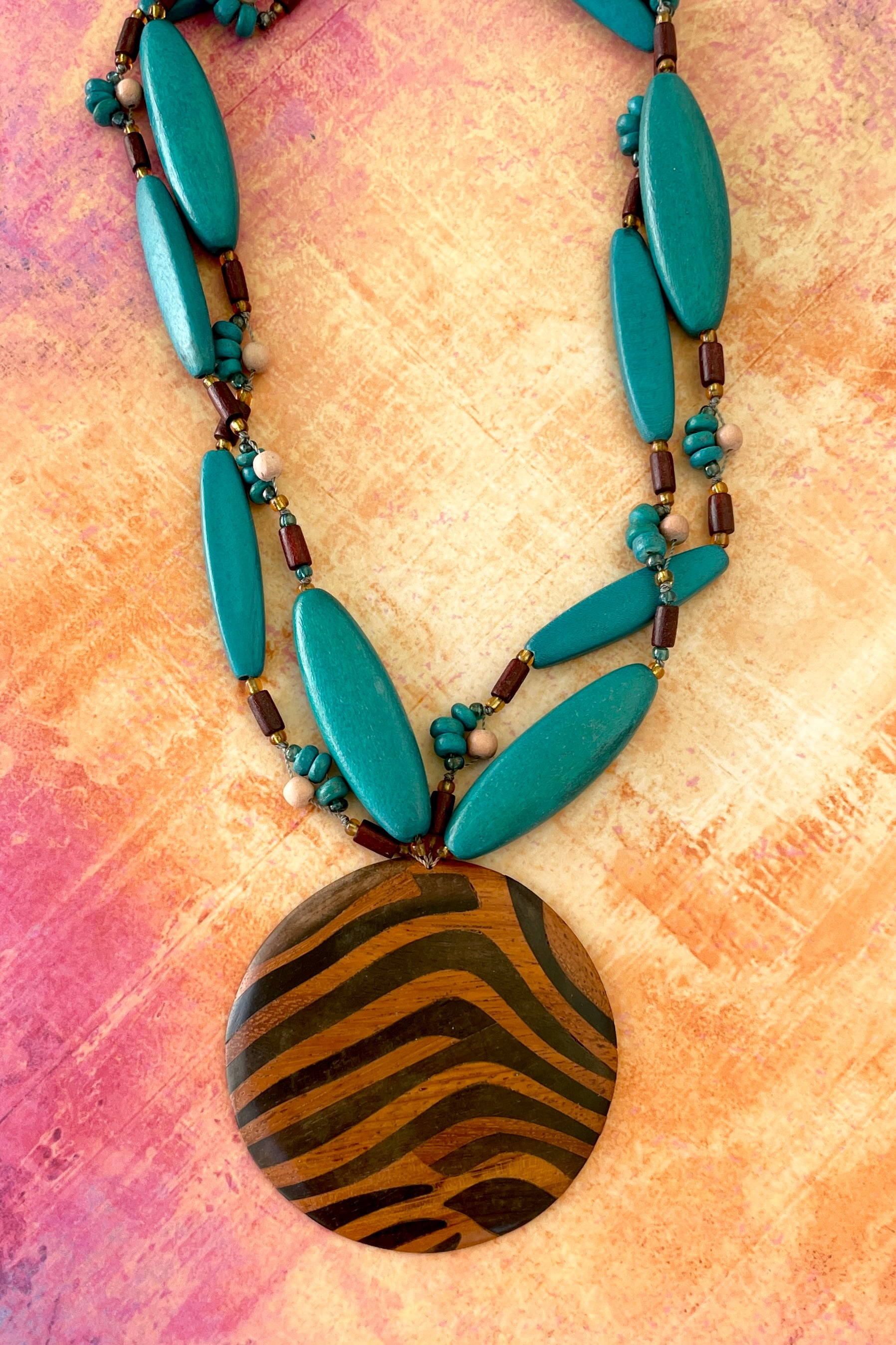 A bright statement necklace with intense coloured wood and glass beads, a centrepiece of beautifully inlaid different colours of wood in an African animal style.