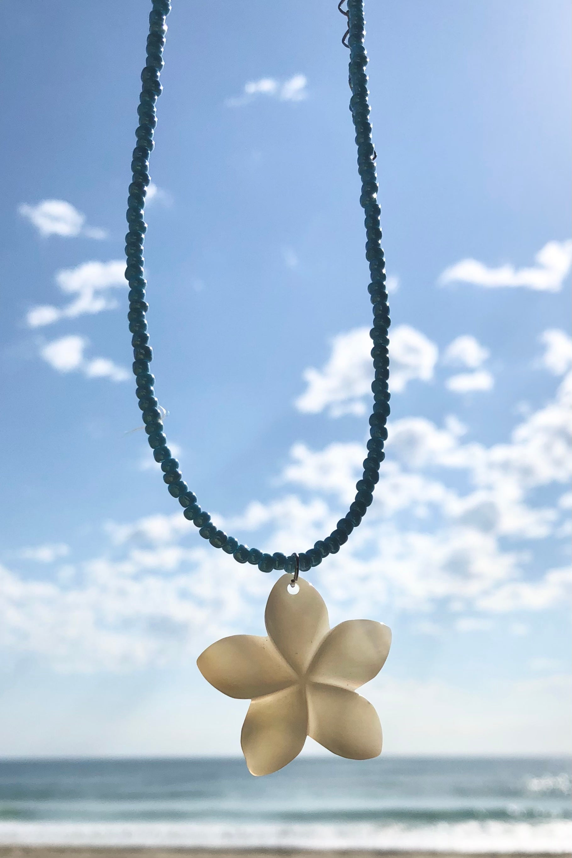 these frangipani flowers hand carved from Mother of Pearl shell all carry the distinctive marks of the artist who created them, no two flowers are ever alike,  strung on pearlescent pale blue glass beads.