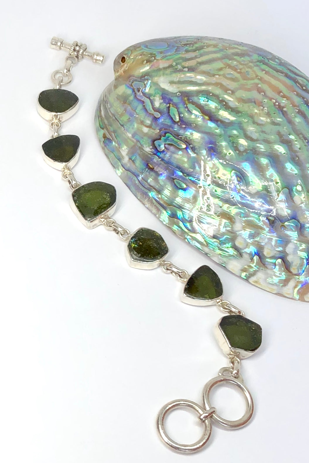Echo Bracelet Tourmaline Green, each of the six stones  has been individually set and rim set into 925 silver.  The stones are all cut and polished into different shapes and linked in 925 silver.