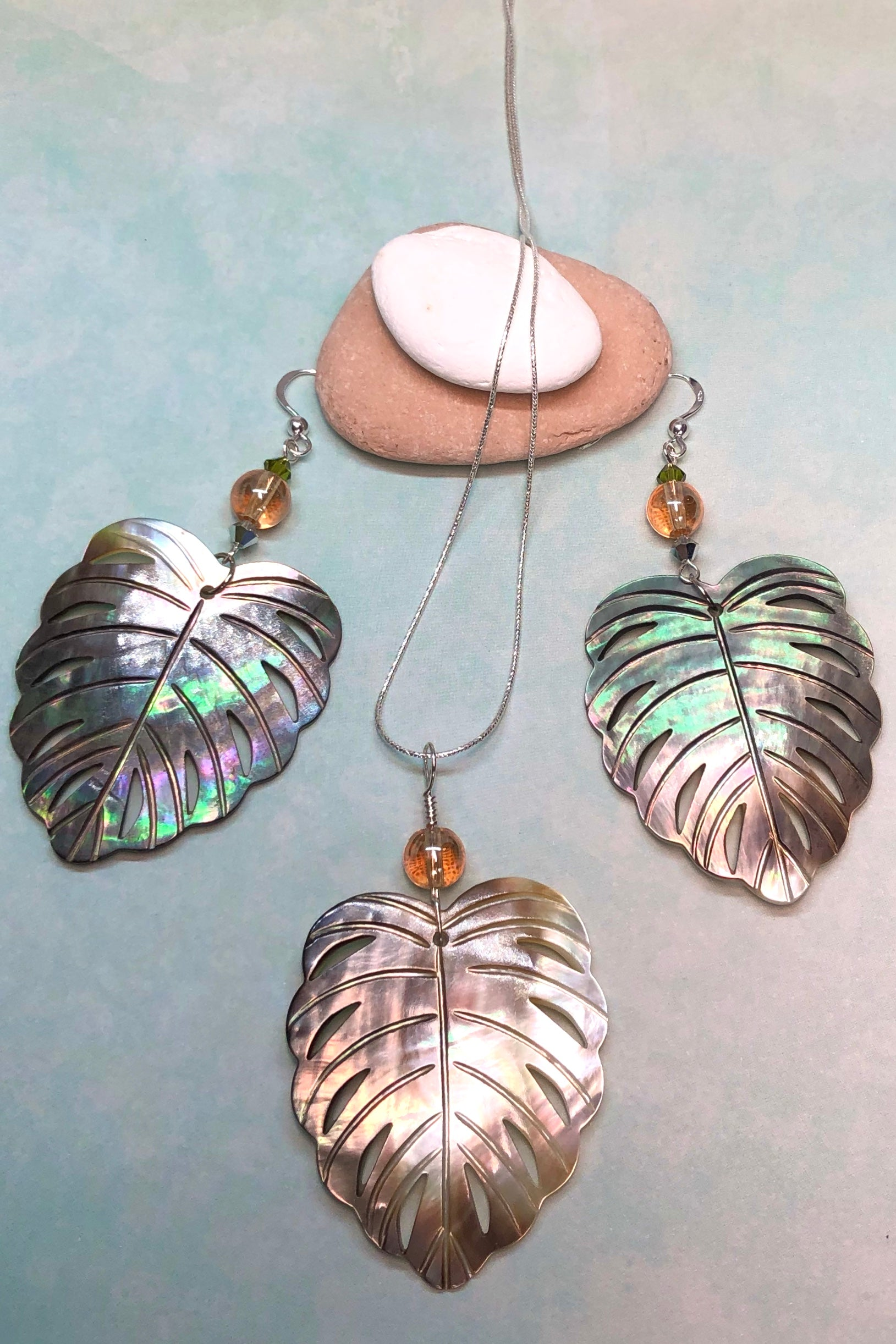 The gorgeous leaf in gold and silvery bronze Mother of Pearl has been hand cut and polished. At the top there is an iridescent crystal bead and a swarovski crystal bead. These earrings are made exclusively for Mombasa Rose