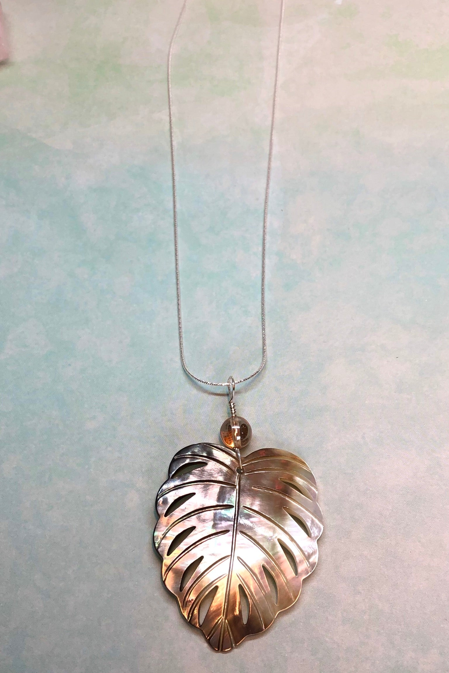 The gorgeous leaf pendant in gold and silvery bronze Mother of Pearl has been hand cut and polished. At the top there is an iridescent crystal bead.