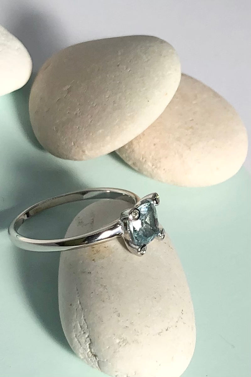 This ring gives a modern twist to antique styling. The lovely square cushion cut and faceted Aquamarine is off set by four one point diamonds