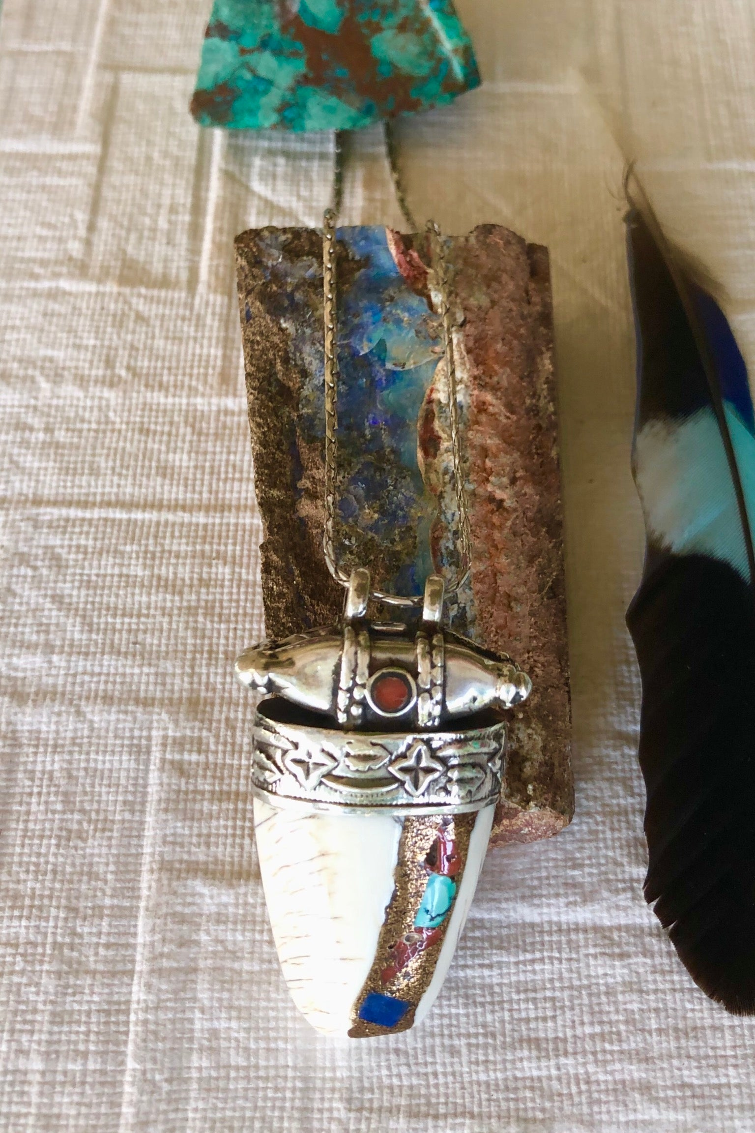 The Echo Pendant Sacred Chank Shell is a really beautiful piece of mystical history featuring unmarked silver cap and bail, Inlaid with coral, turquoise and lapis Lazuli.
