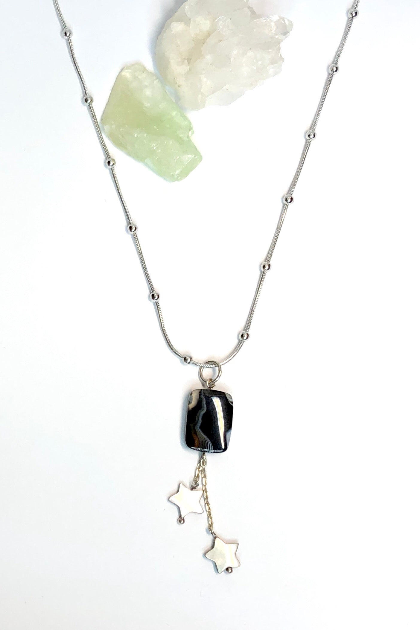 A little bit of night mystery and magic in our Echo Gems pendant black stars featuring one off handmade pendant, silvery colour bobble chain, natural black banded agate gemstone and two hand cut mother of pearl stars hang off silver chain.