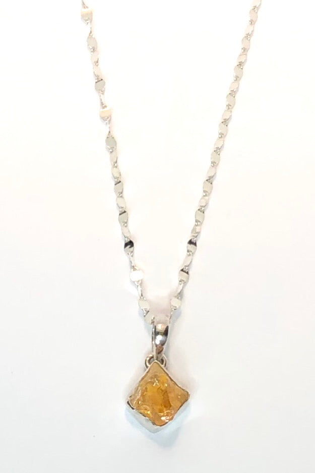A 2.5cm long Piece of natural rough citrine gemstone hand set into 925 silver coming on a 45 cm silver flutter chain.