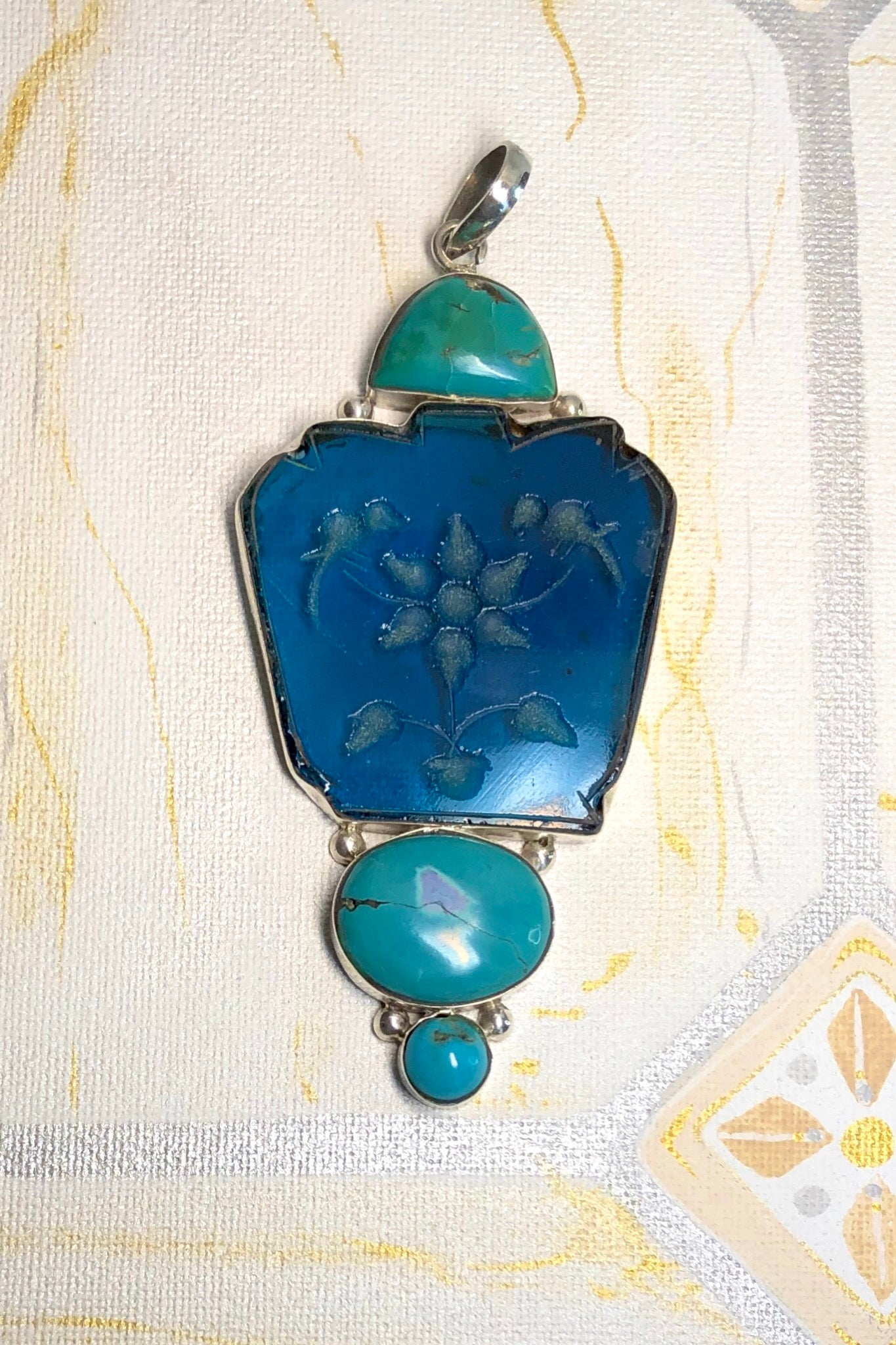 Echo Intaglio Blue Pendant is a mystical and historical pendant featuring Unsymmetrical cut turquoise glass intaglio and each piece has been set in silver.