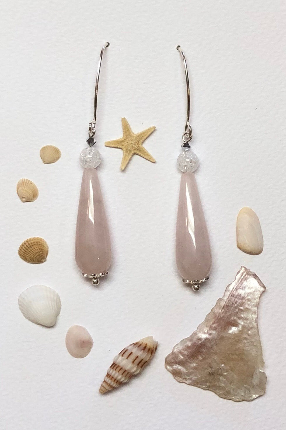 Approximately 6cm length.  Drop style earrings. 925 silver hook earrings. Pale pink Rose quartz teardrop shaped stone with a single crackle rock crystal bead on top.