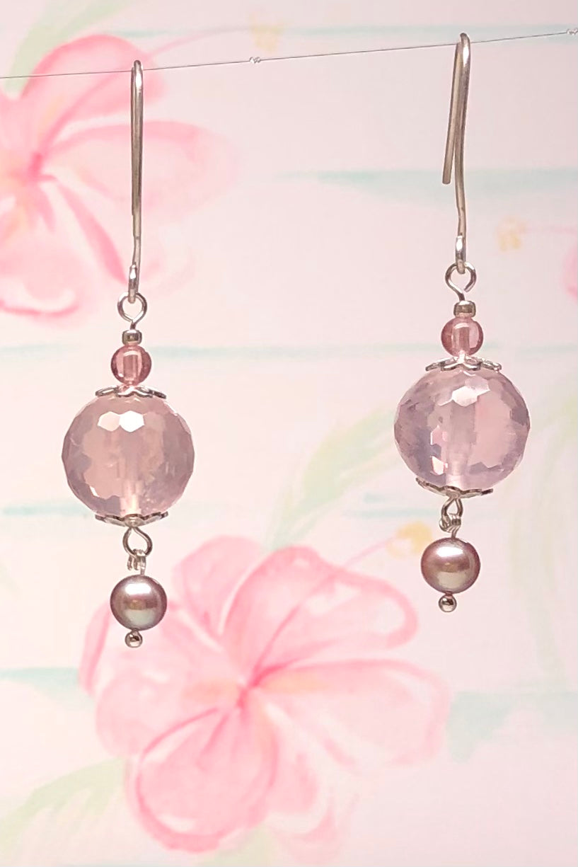 A divine pink Rose Quartz ball that has multi hand cut facets, suspended is a natural pearl in a soft silvery pink, the hook is 925 silver.