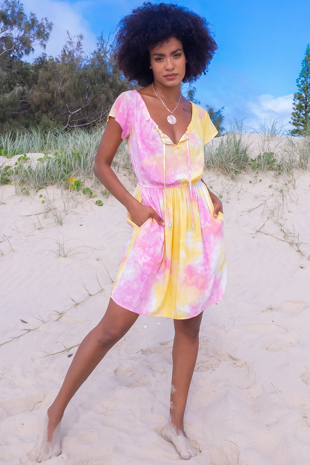 The Ace Gelati Tie Dye Dress features adjustable neckline with ties, elasticated waist, side pockets and 100% rayon in pink and yellow tie dye.