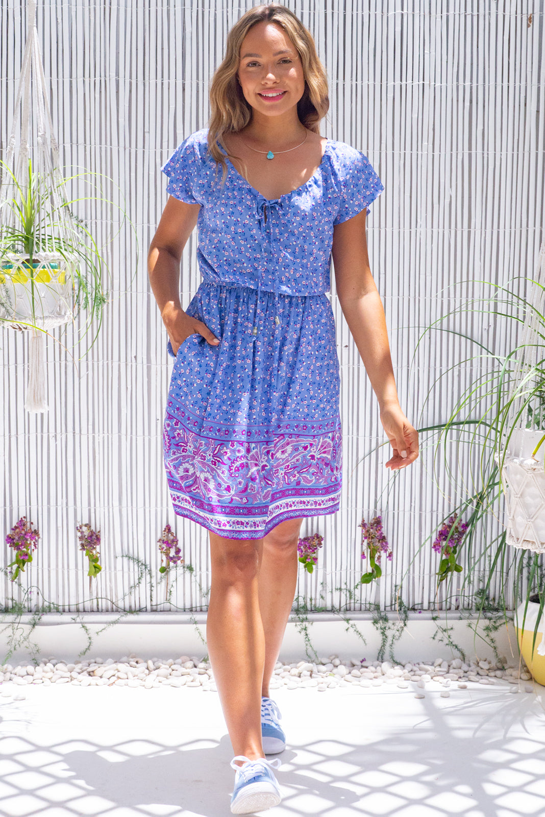 The Ace Maya blue Dress will become your favourite day dress featuring adjustable neckline with ties, cap sleeves, elasticated waist, side pockets and 100% rayon in soft, purply blue base with small floral accents and border feature.