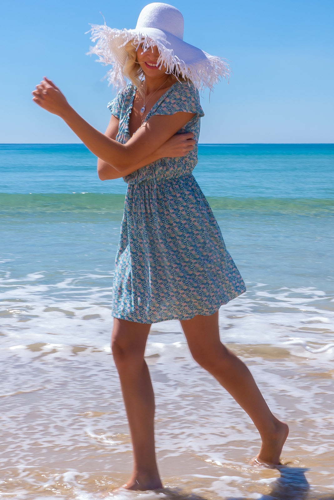 The Piccadilly Blue Dress features adjustable neckline with ties, cap sleeves, easticated waist, side pockets and 100% rayon in blue, pink, green and white print.
