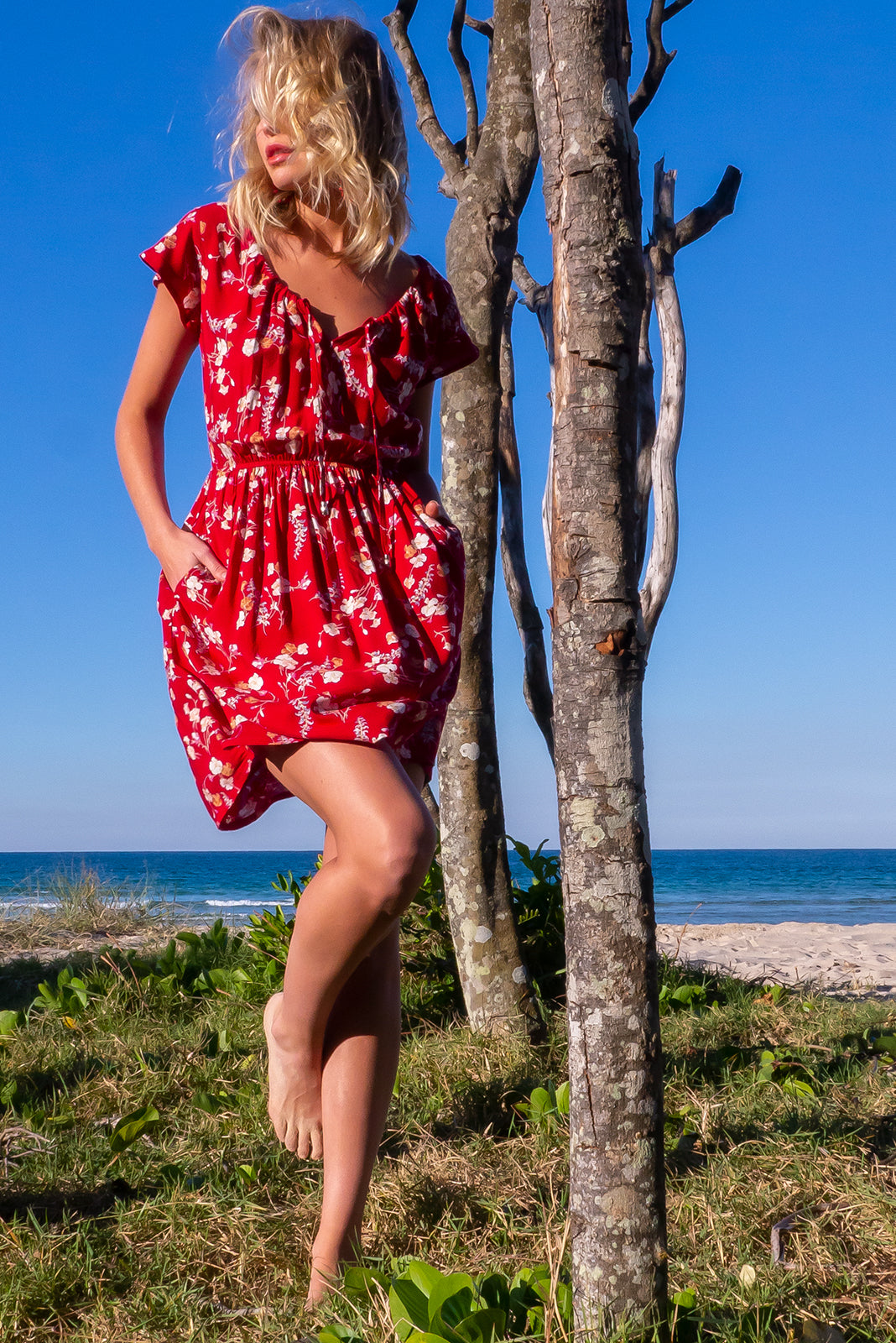 The Ace red Lava Dress has adjustable neckline with ties, cap sleeves, elasticated waist side pockets and 100% viscose in deep red base with vintage floral print.