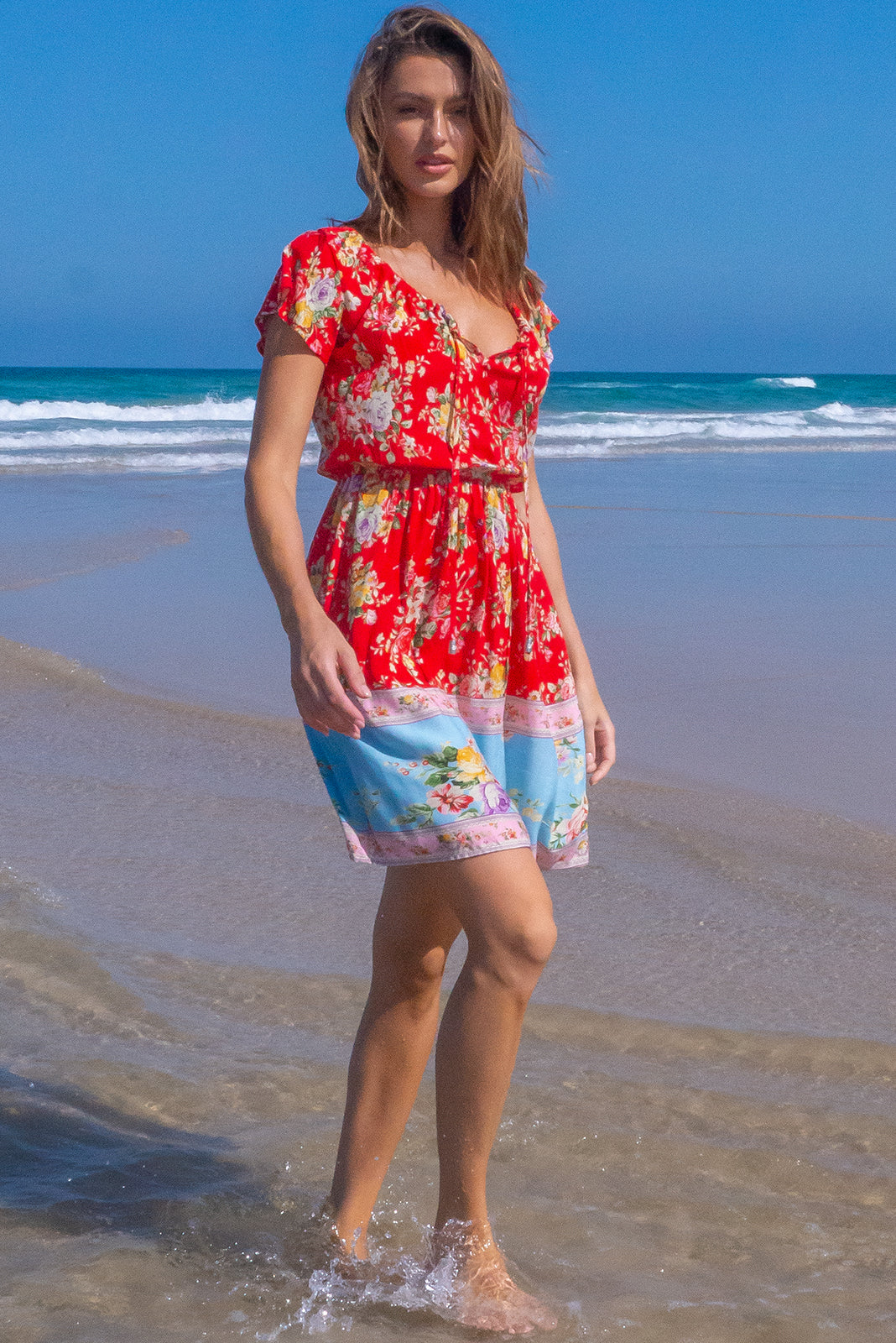 The Ace Red Roses Dress features adjustable neckline with ties, cap spire sleeves, elasticated waist, side pockets and 100% rayon in red base with vintage ind floral print and border detail.