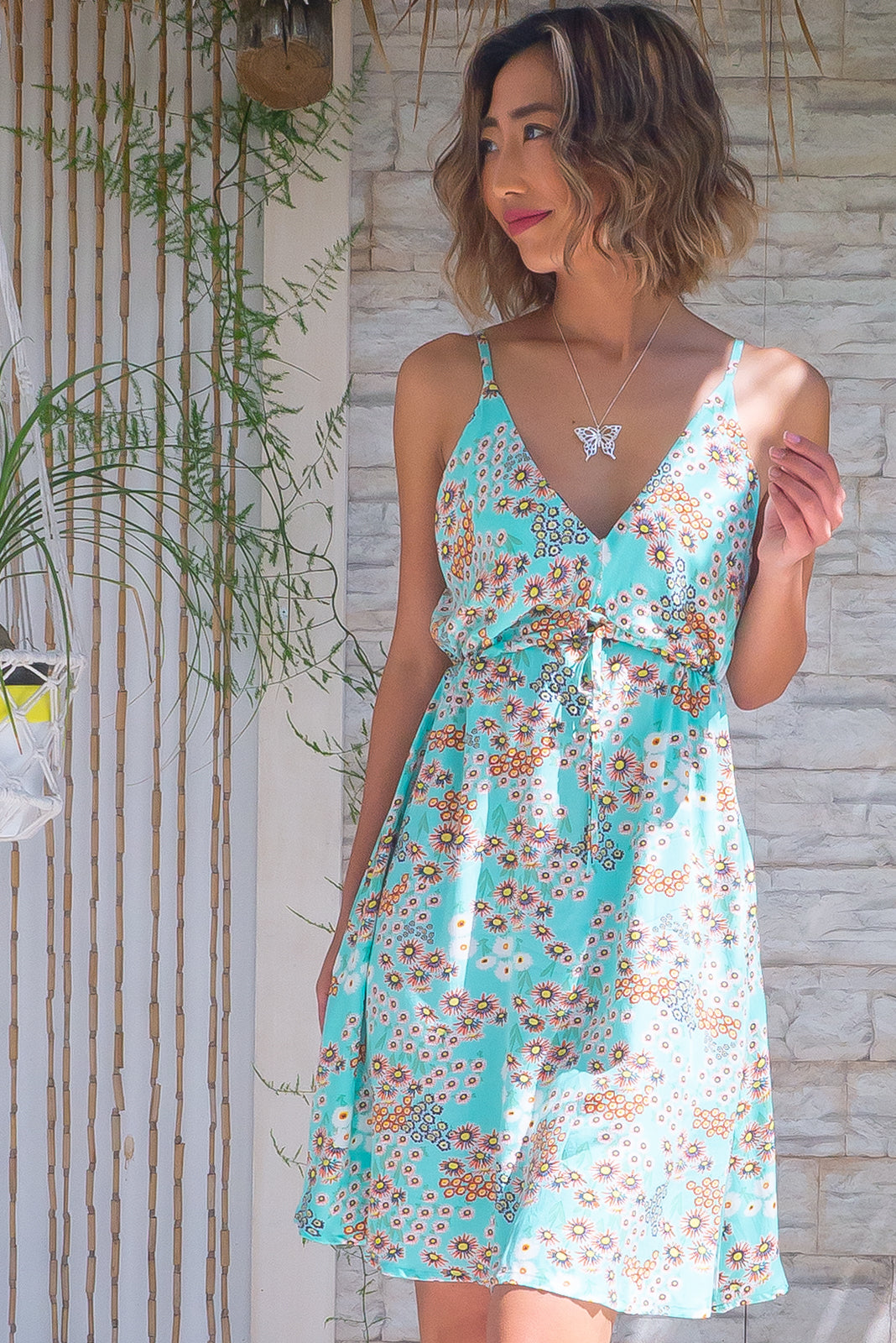 The Adora Sky Mint Mini Dress has V neck and back, elastic and drawstring under bust, adjustable, thin straps, side pockets, wavy, uneven hemline and 100% rayon in fresh, aqua/mint base with retro orange and white floral print.