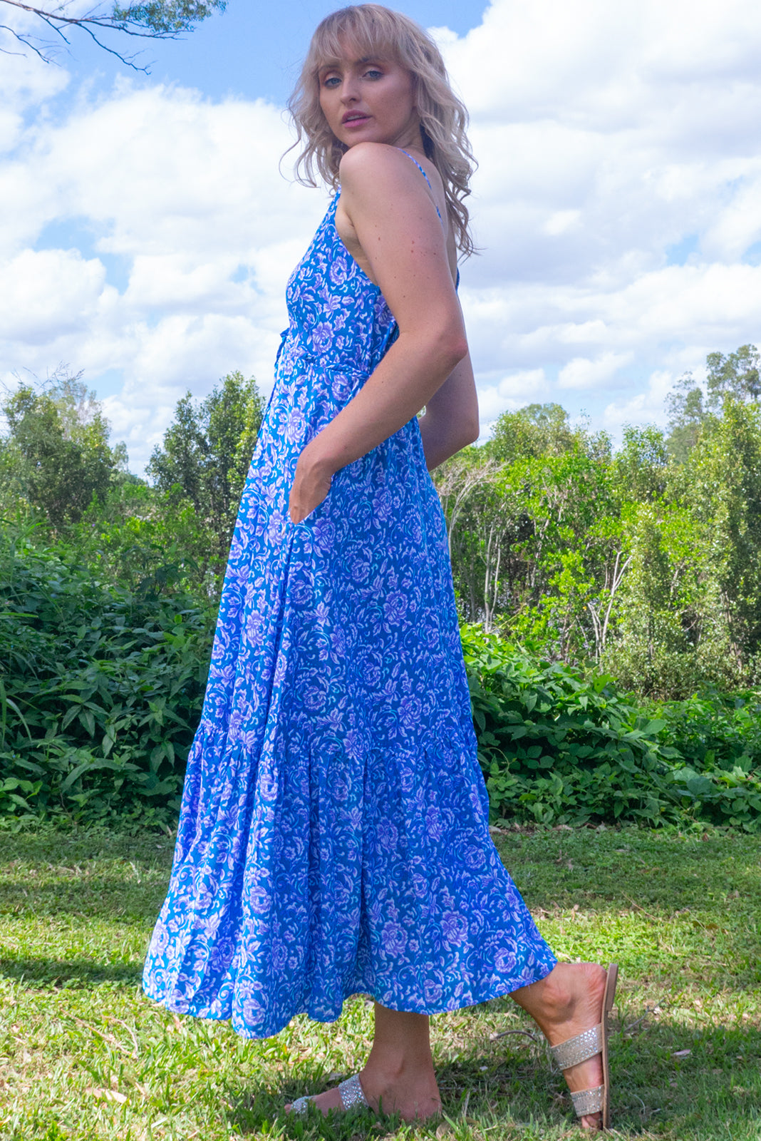 The Adoro Turquoise Fleur Maxi Dress features bust area lined, V neck and back, drawstring under bust, thin straps, side pockets, frill at base of skirt and 100% rayon in blue base with white and purple floral print.