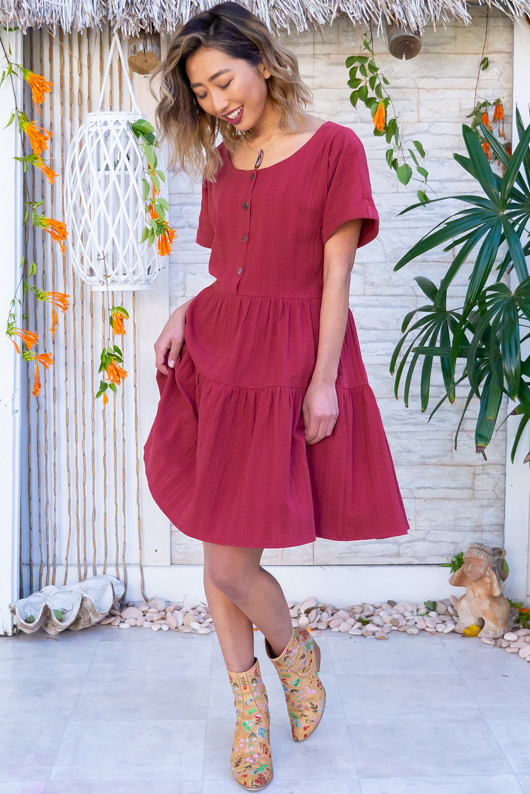 The Airlie Berry Red Mini Dress features functional button down chest to waistline, two-tiered gathered skirt, adjustable button plackets at back to cinch waist, side pockets and woven 100% cotton in Wine red colour.