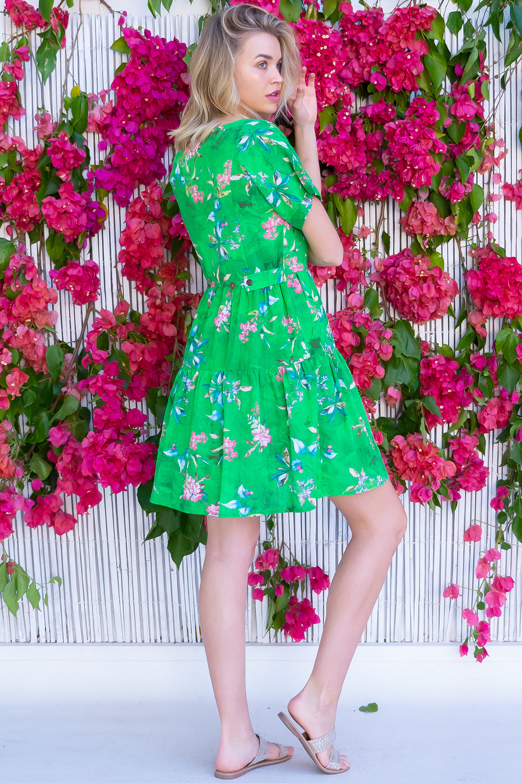 The Airlie Secret Garden Green Mini Dress features functional button down chest to waistline., two-tiered gathered skirt, adjustable button plackets at back to cinch waist, side pockets and 100% cotton in vivid green tie dye effect base with floral print.