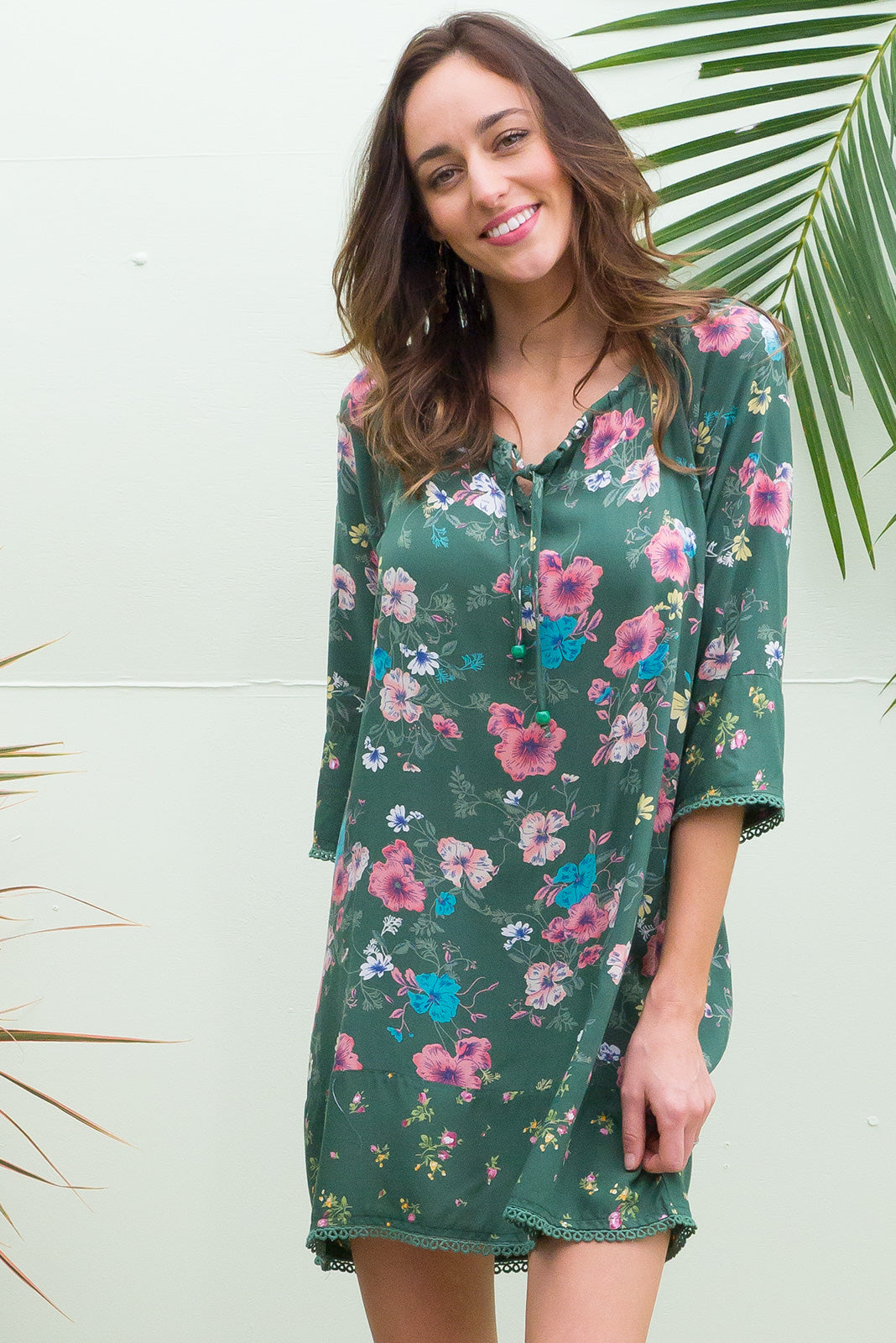 Angie Dee Tunic Dress with a elastic drawstring neckline and midi sleeve with cotton lace trim on the sleeve and hem in a green floral print on smooth soft rayon