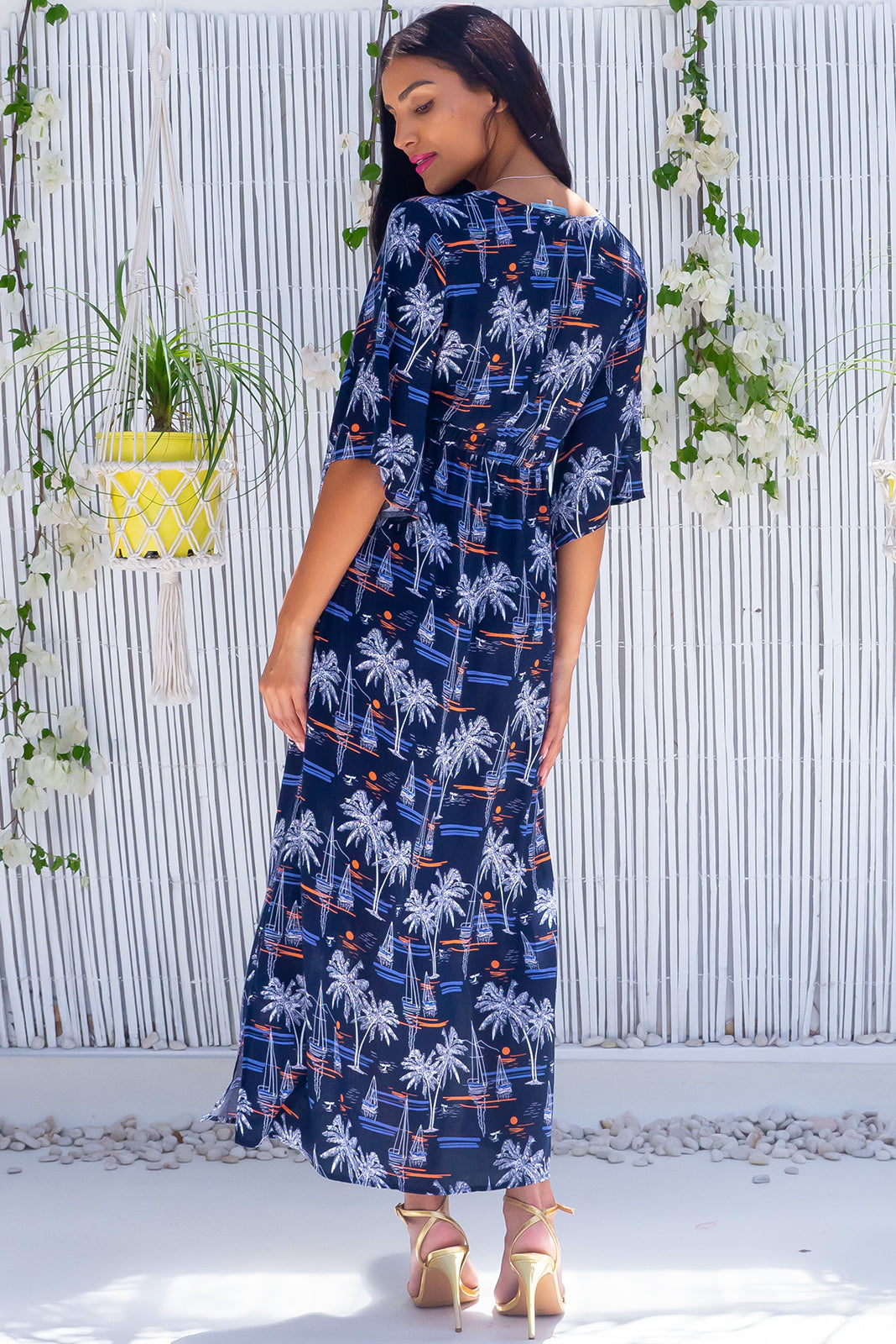 The Annabella Bali Harbour Navy Caftan Maxi Dress features deep V-neckline, side pockets, braided multicoloured drawstring with tassels and bead and 100% rayon in navy base with palms and boat print.