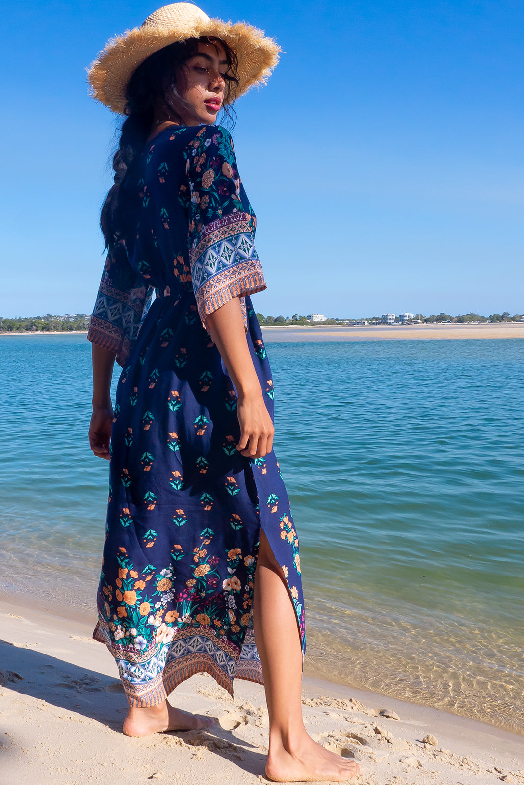 The Annabella Navy Bordure Fleurie Caftan Maxi Dress features deep V-neckline falling below a standard bra line, side pockets, elasticated waist back. Braided multicoloured drawstring with tassels and beading and 100% rayon in navy base with floral print and border feature.
