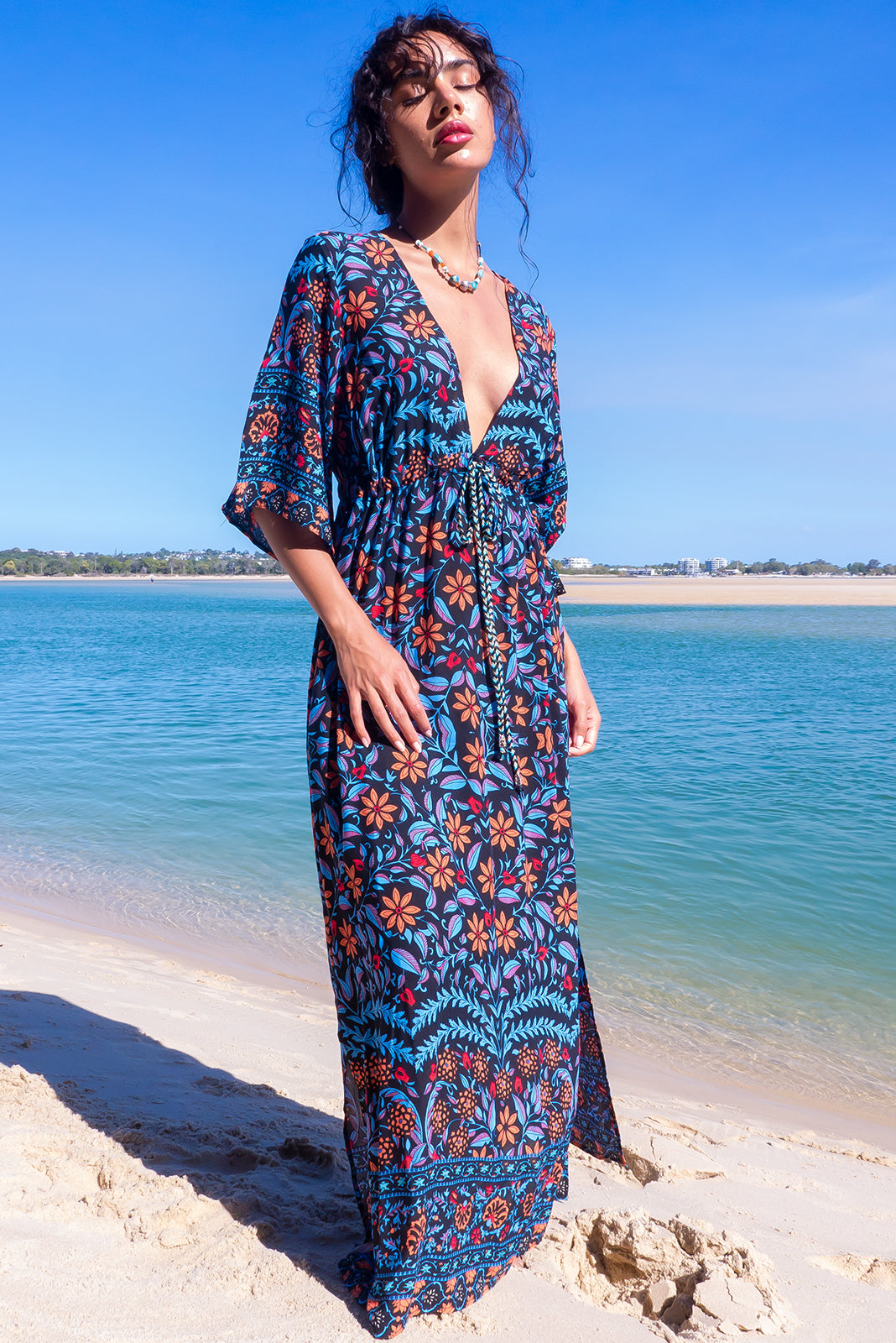 The Annabella Noir Nuit Caftan Maxi Dress features deep V-neckline, side pockets, front drawstring waist, elasticated waist back, braided multicoloured drawstring with tassels and beading and 100% rayon in ink base with floral motif and border feature.