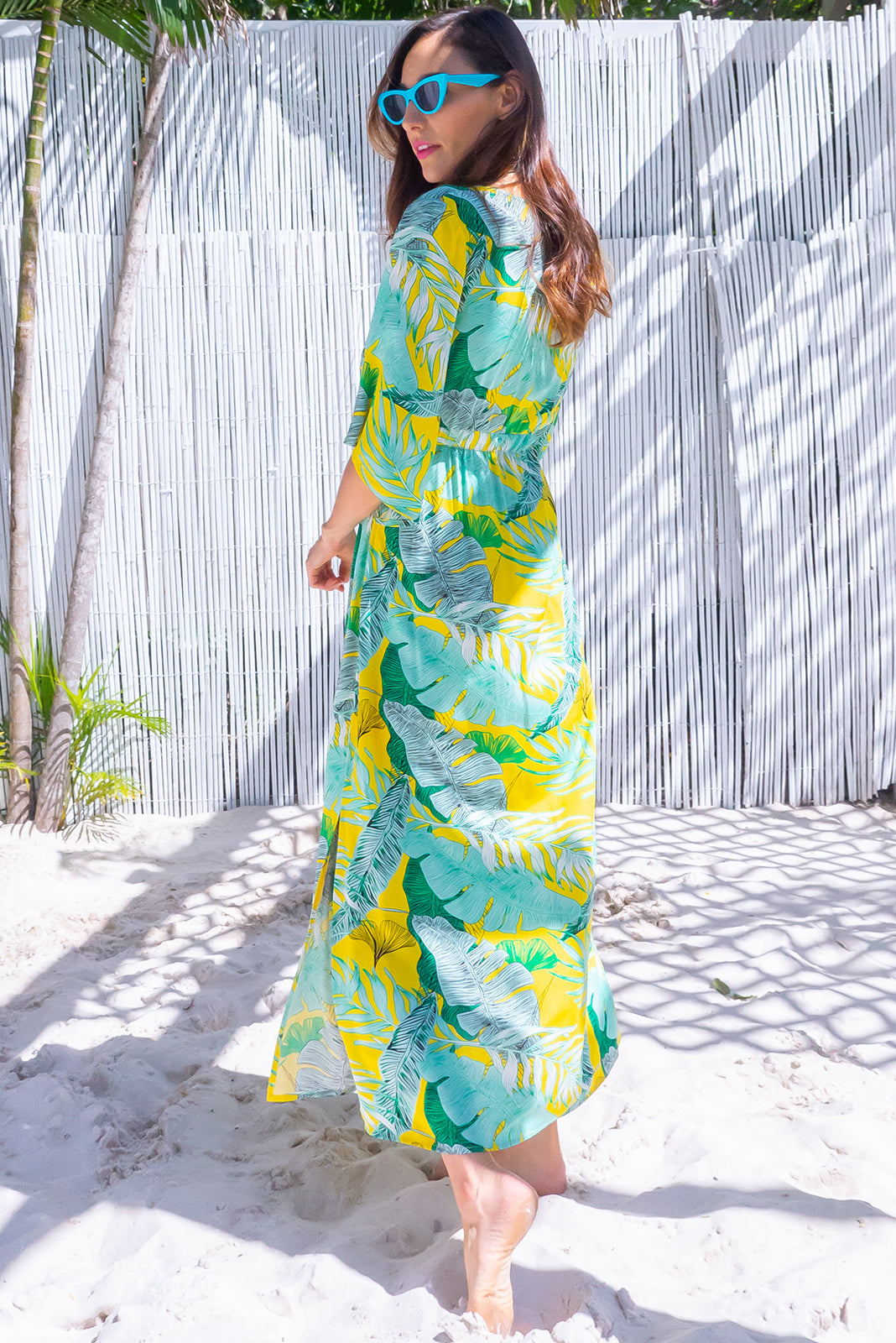 The Annabella Palm Gold Caftan Maxi Dress is a deep V-neckline beach dress featuring side pockets, braided multicoloured drawstring with tassels and bead and 100% rayon in bright yellow base with green palm print.