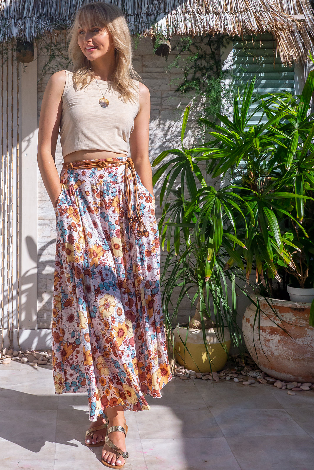 The Atlantis White Gold Maxi Skirt features double V-shaped waist yoke, inset panels from the yoke down, elasticated/shirred back of waist, side pockets, shapely hemline and 100% viscose in cream base with large vintage inspired floral print.