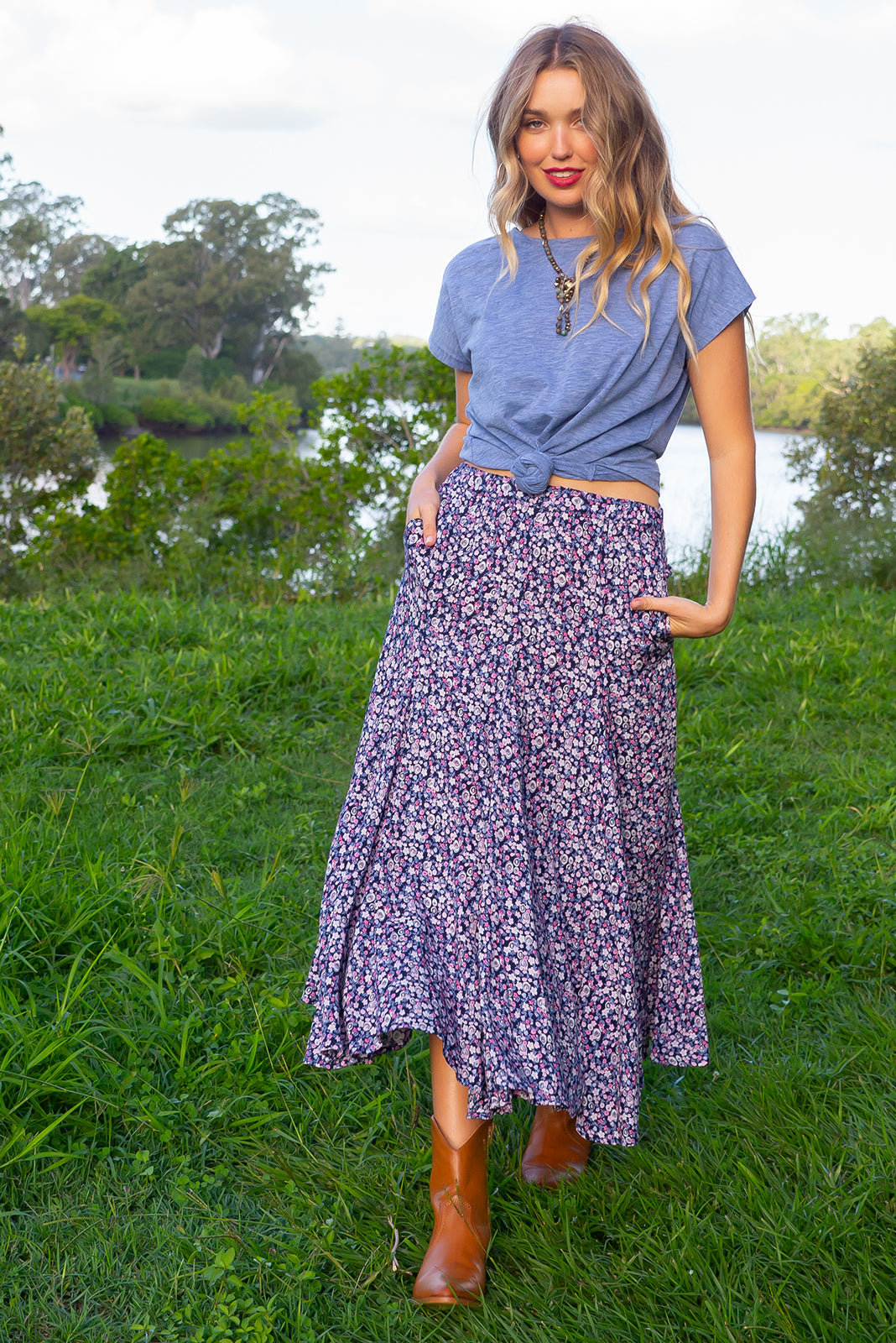 Avalon Alchemy Midi Skirt has elastic waistband which is fitted over the hips and waist but features full fishtail inserts for a full soft finish at the hemline made in a woven non stretch 100% rayon of inky base with a purple toned ditzy floral print.