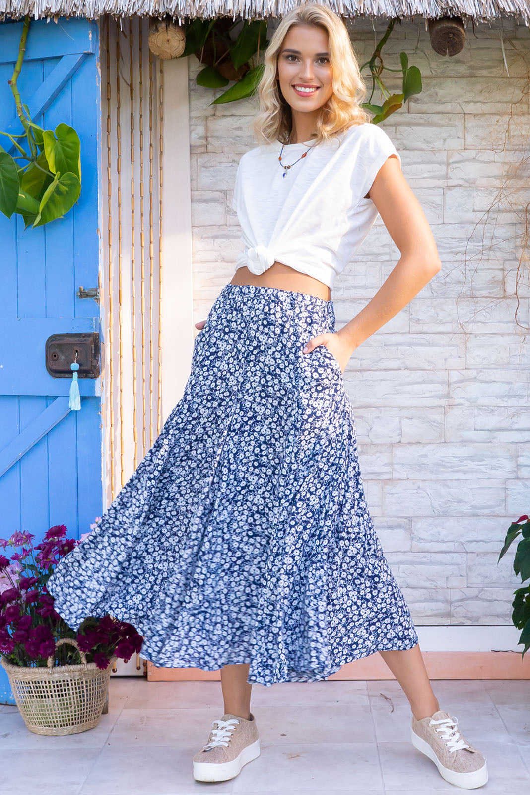 Avalon Anise Navy Midi Skirt has an elastic waistband is fitted over the hips and waist but features full fishtail inserts for a full soft finish at the hemline. It comes in a woven non stretch 100% rayon with and features blue base with a dtizy white floral print