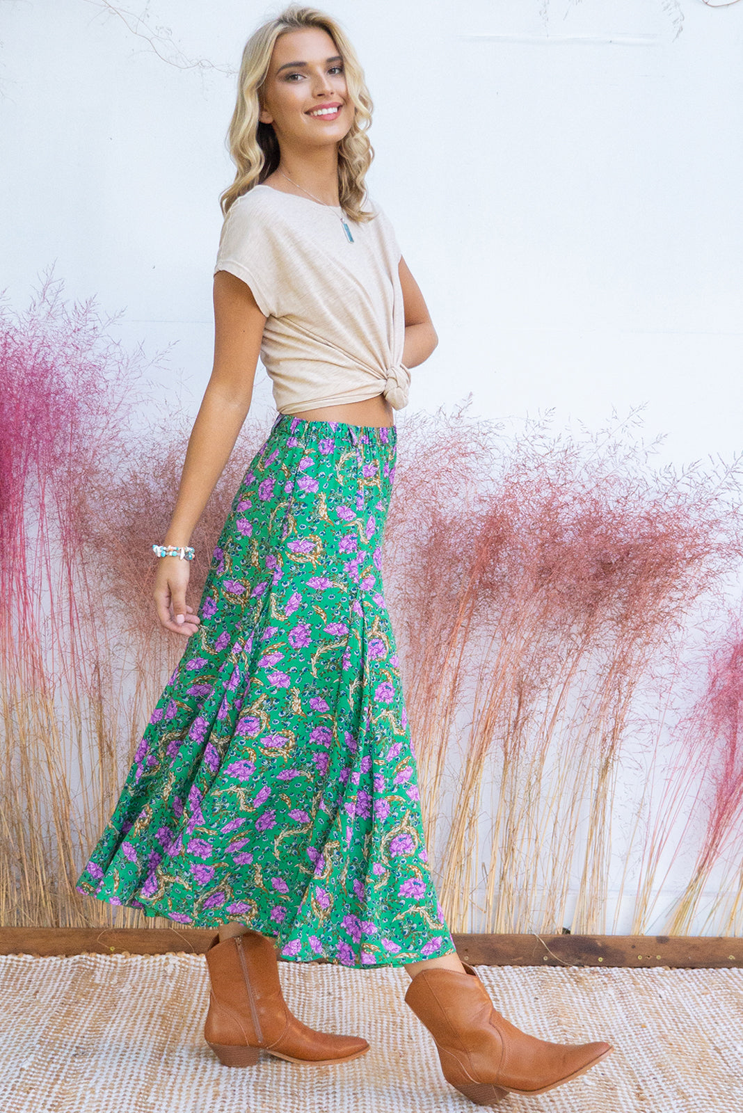 Avalon Gandalf Green Midi Skirt has an elastic waistband is fitted over the hips and waist but features full fishtail inserts for a full soft finish at the hemline. It comes in a woven non stretch 100% rayon with and features apple green base with a purple bohemian eastern inspired floral print