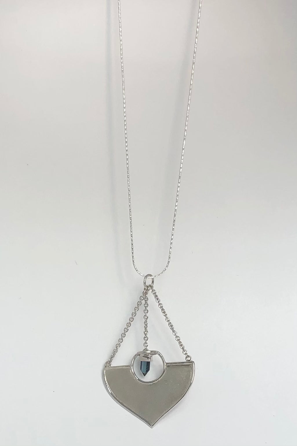 A stunning African Style 925 silver pendant with a Tourmaline Shard which hangs perfectly through a silver circle. The intense blue Tourmaline was sourced ethically from miners in Nigeria,
