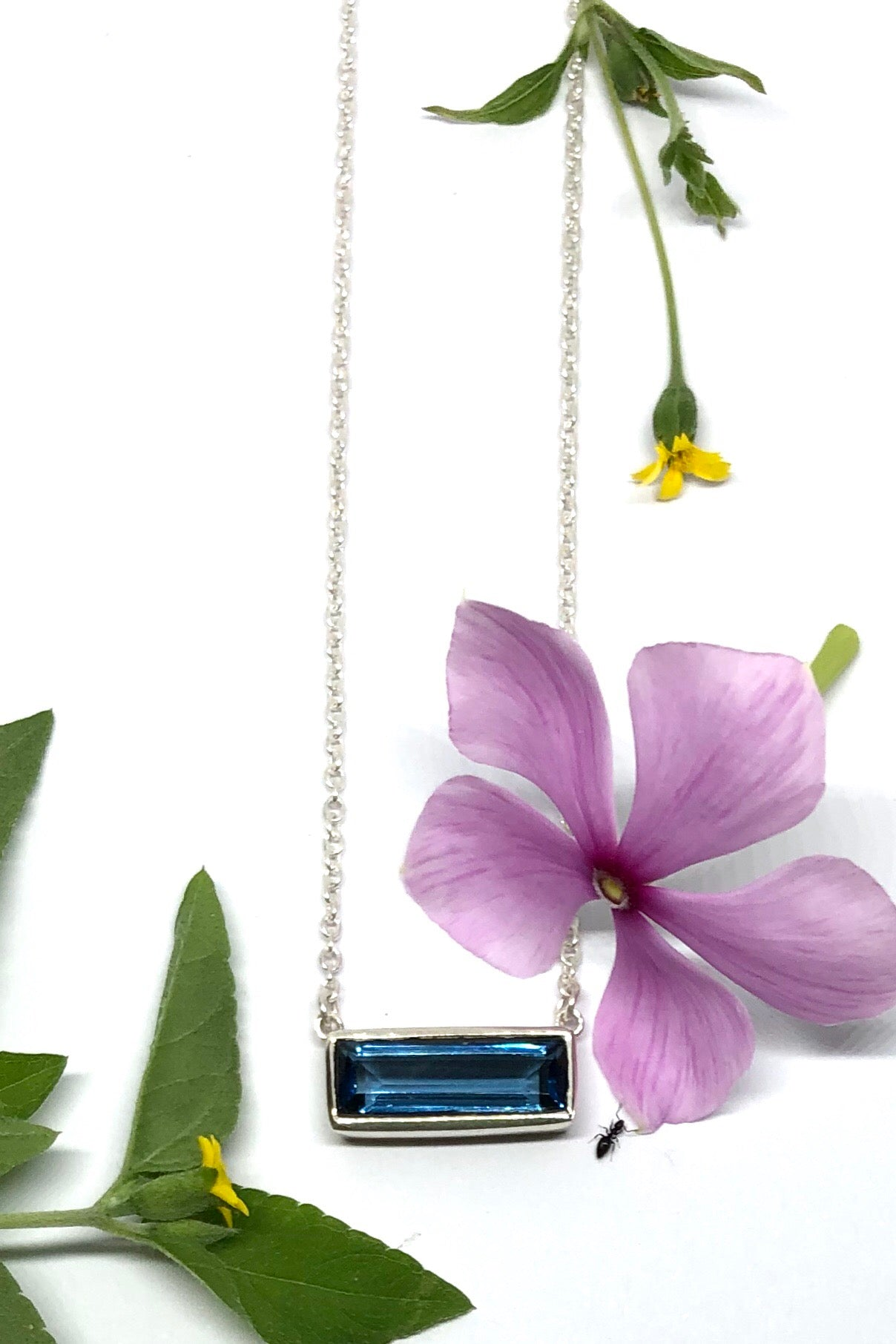 The Oracle Necklace Gems in Montana Blue is delicate little rectangle design, approximate 1.5cm wide, 925 solid silver surround and comes on a 925 silver chain.