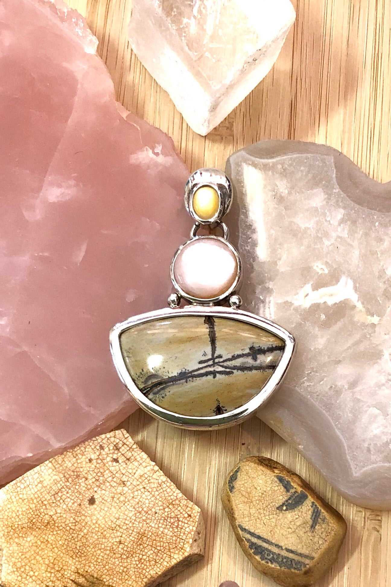 Echo Jasper Picture Stone Pendant is a beautiful pendant set with two cabochons of delicate millions of years old Mother of Pearl.