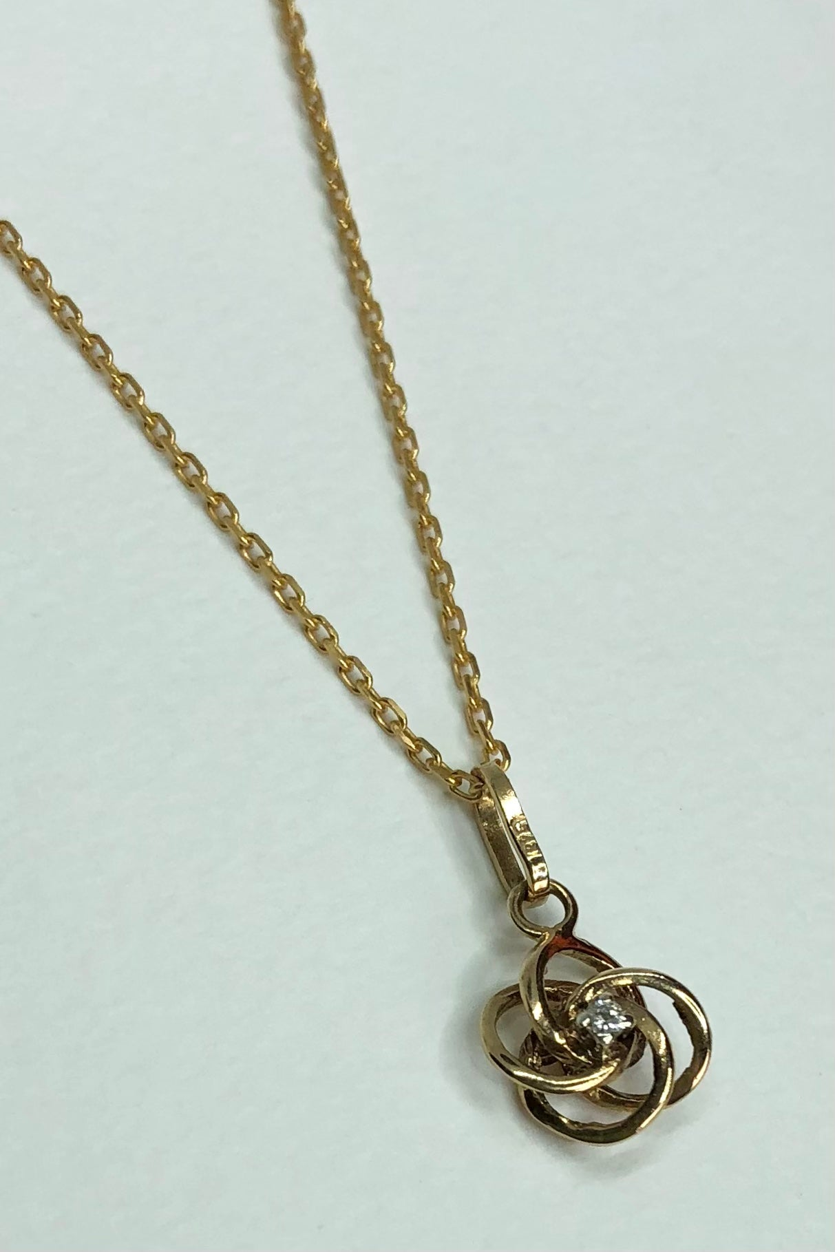 This super sweet vintage pendant  diamond knot has four linked circles with a tiny diamond in the centre.