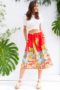 Bahama Skirt Island Red is a midi length skirt with an elasticated waist, deep side pockets, and pleats it features a bright navy base with a bright red seaside scene on woven 100% rayon