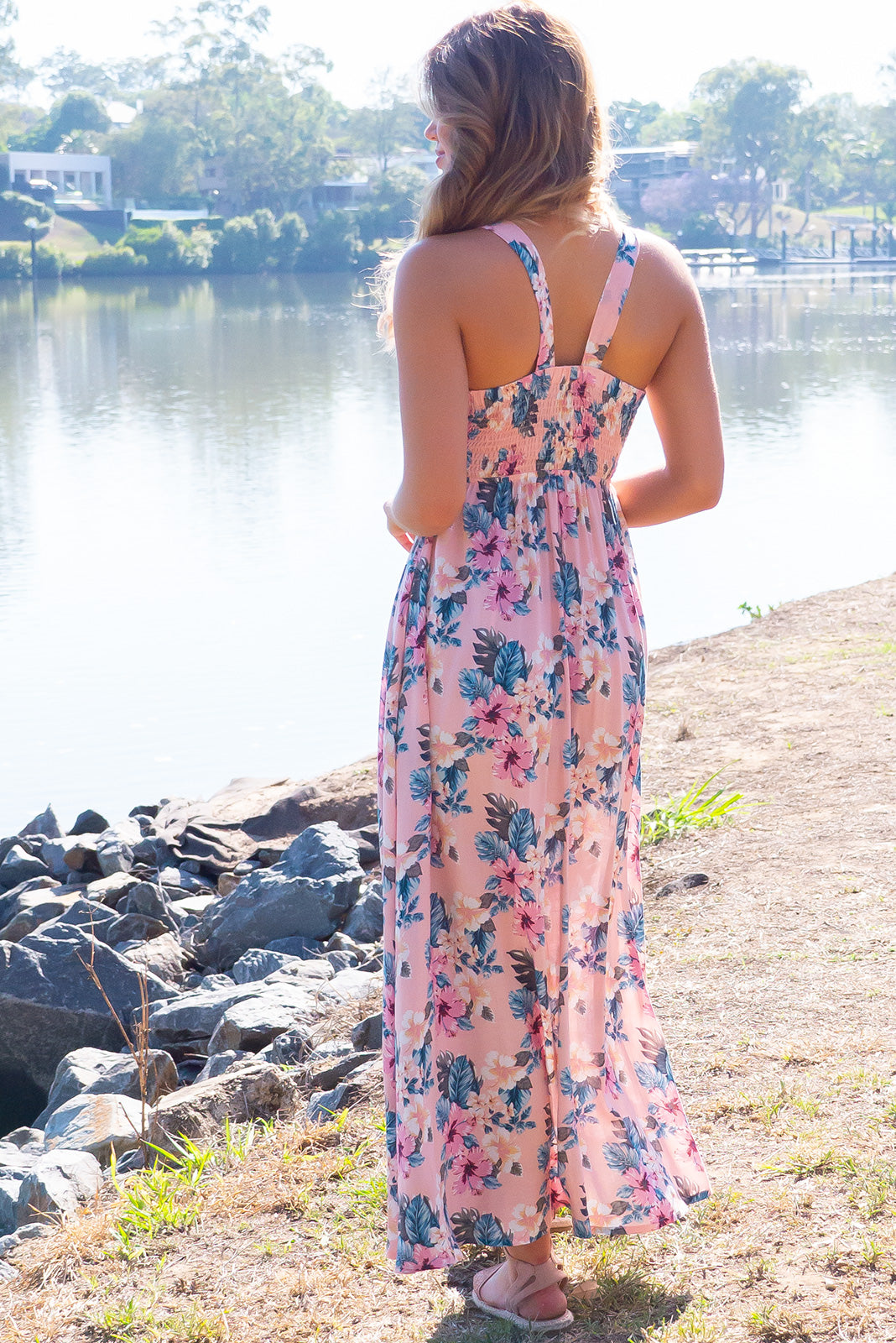 Ballito Bay Island Pink Maxi Dress, bohemian summer style, 100% rayon, lightweight sheer fabric, elastic shirring across back, sleeveless, keyhole tie design on bust, side pockets, pastel pink base with large pink, teal and white floral pattern.