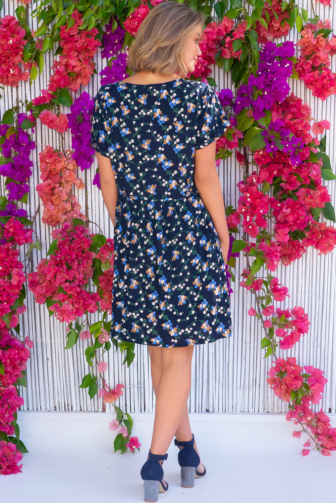 The Blue Moon Blooms Noir Dress is a lightweight loose frock featuring cuffed sleeves, drop waist, buttons and tabs at waist, side pockets and 100% rayon in ink base with floral print.